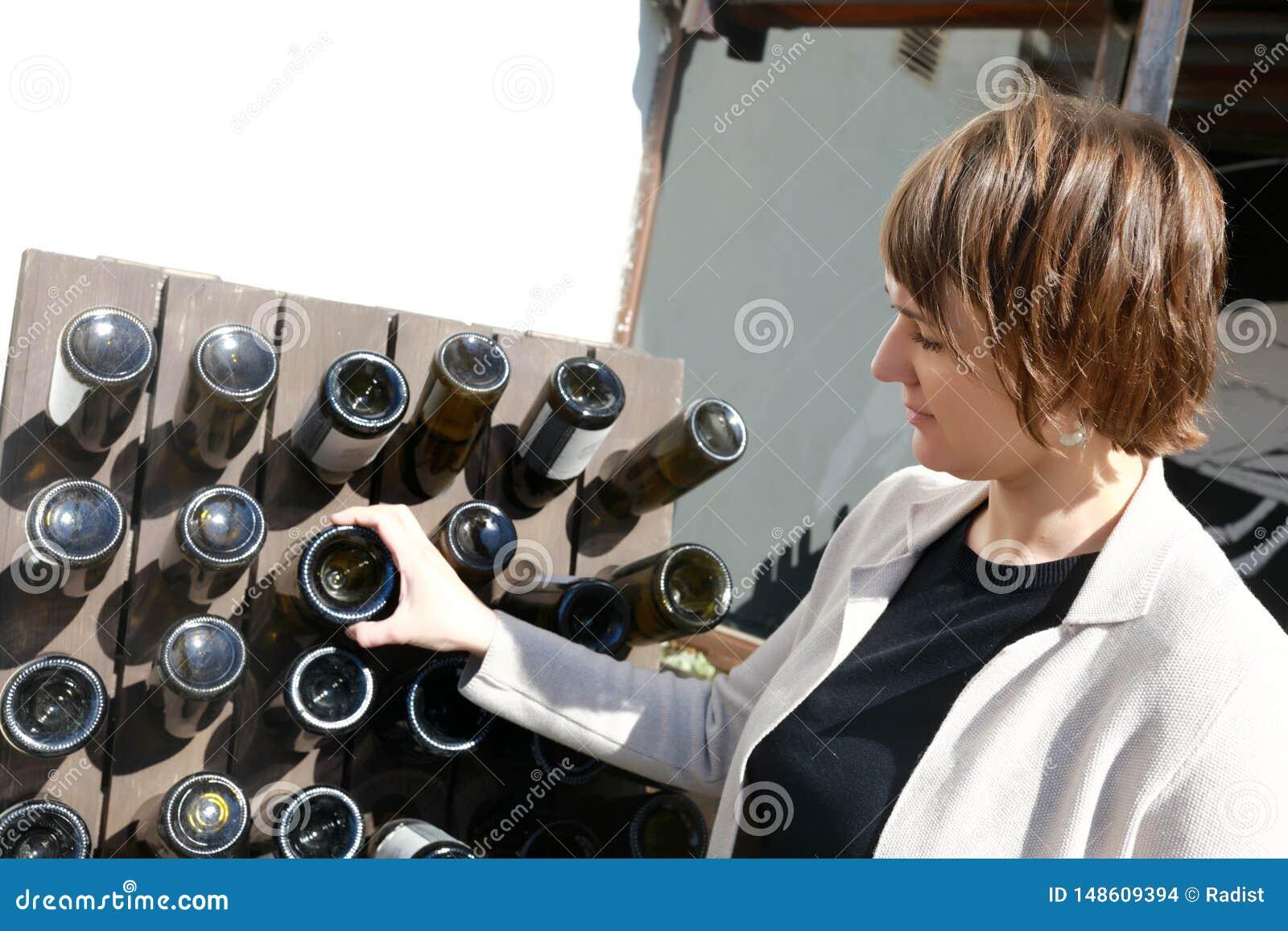 Γυναίκα σχετικά με το μπουκάλι κρασιού