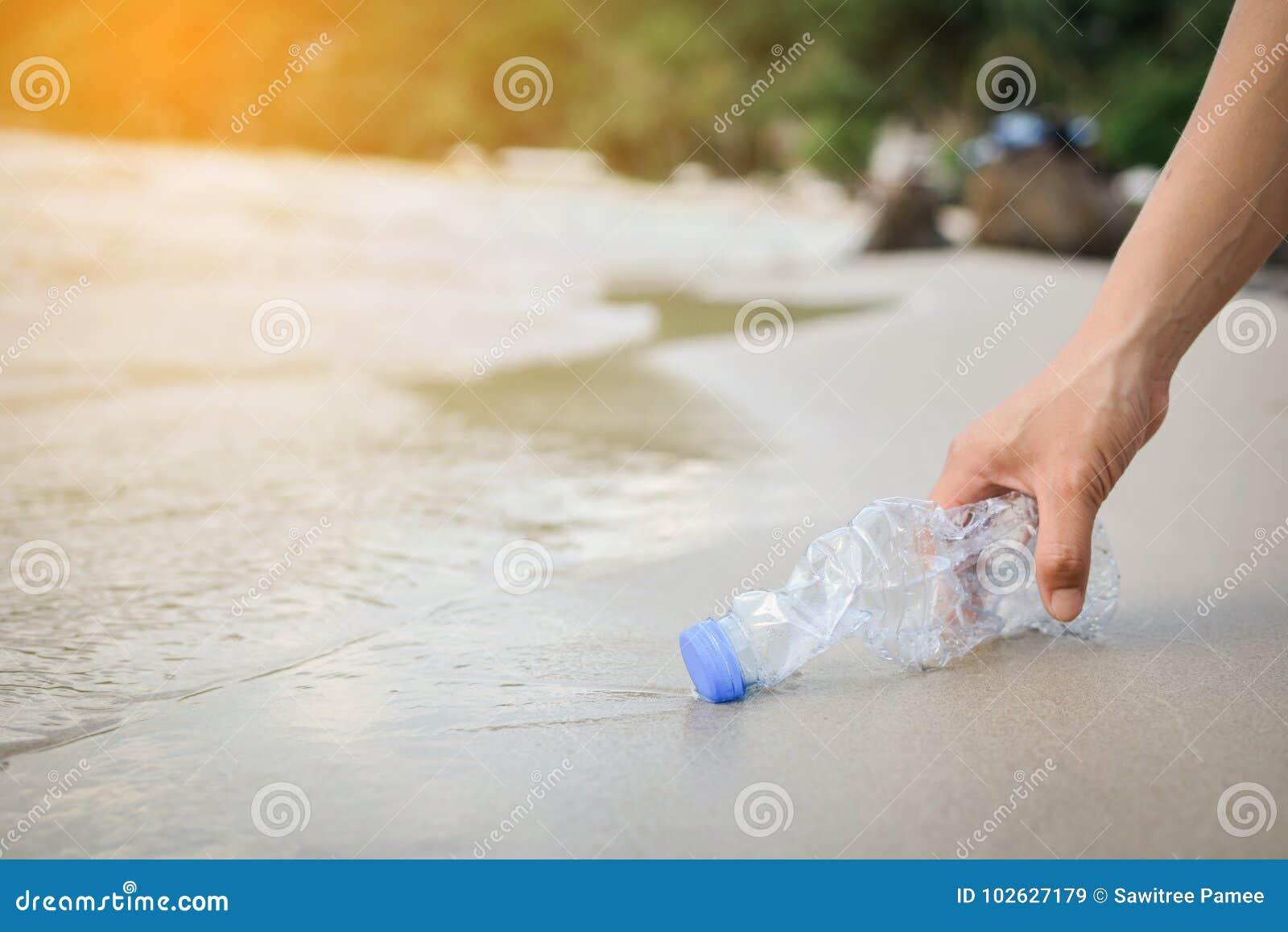 Γυναίκα χεριών που παίρνει τον πλαστικό καθαρισμό μπουκαλιών στην παραλία