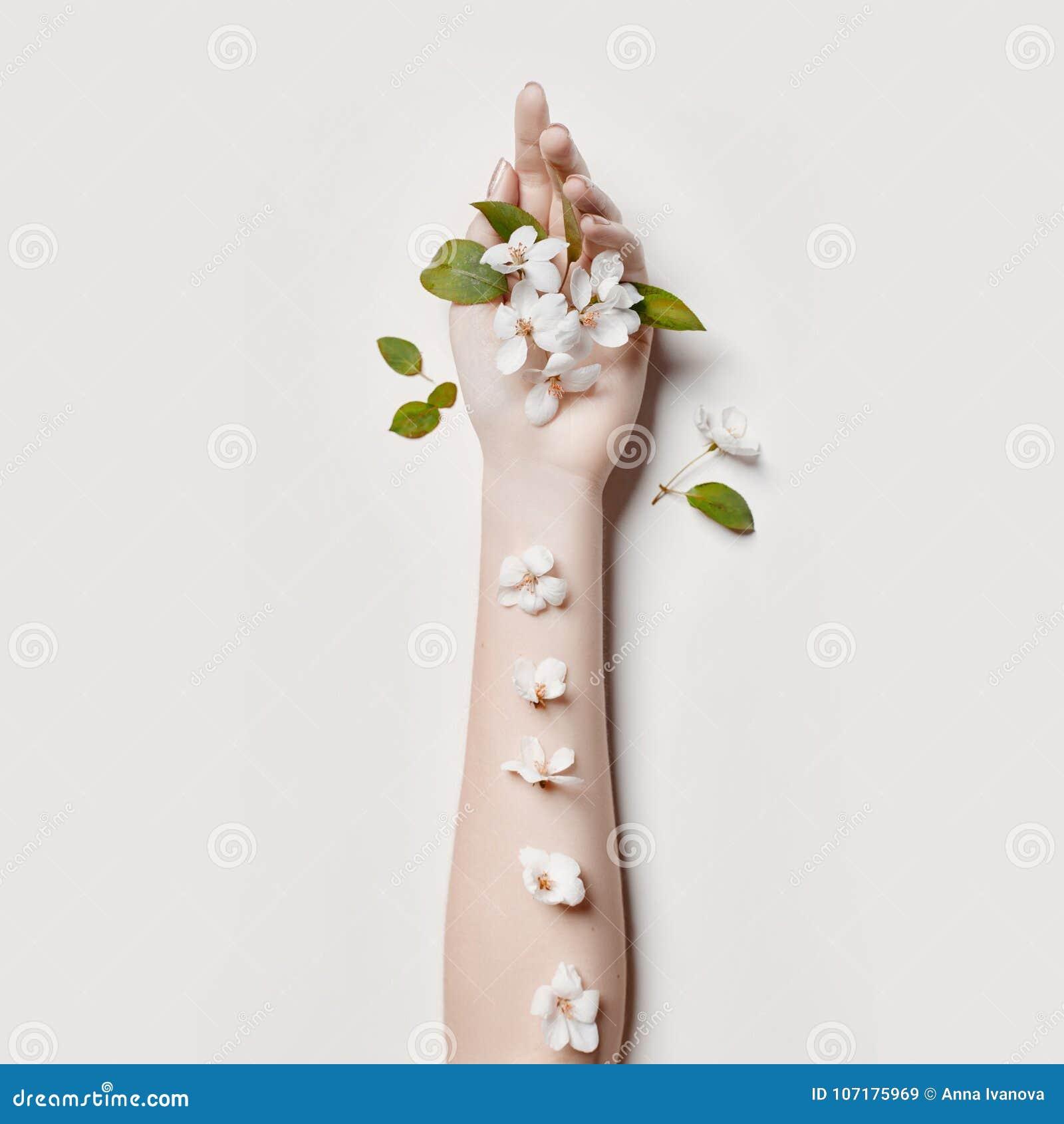 Γυναίκα χεριών τέχνης μόδας στο θερινό χρόνο και λουλούδια σε ετοιμότητα της με τη φωτεινή αντιπαράθεση makeup Δημιουργικά κορίτσ
