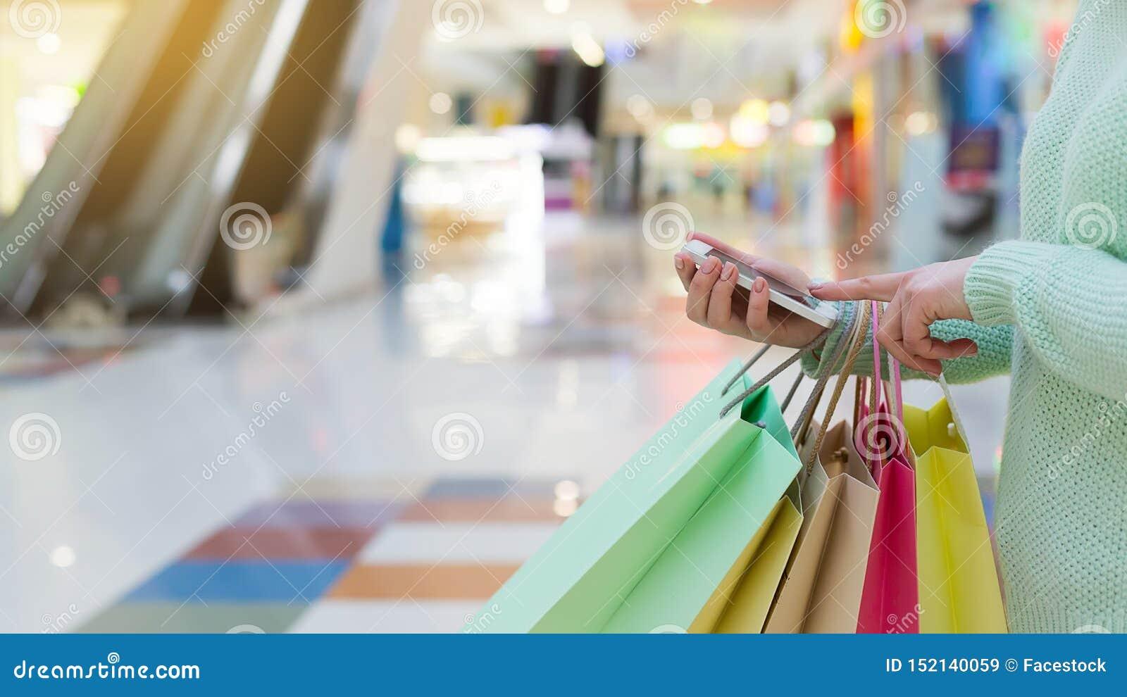Γυναίκα χρησιμοποιώντας το smartphone και κρατώντας τις τσάντες αγορών