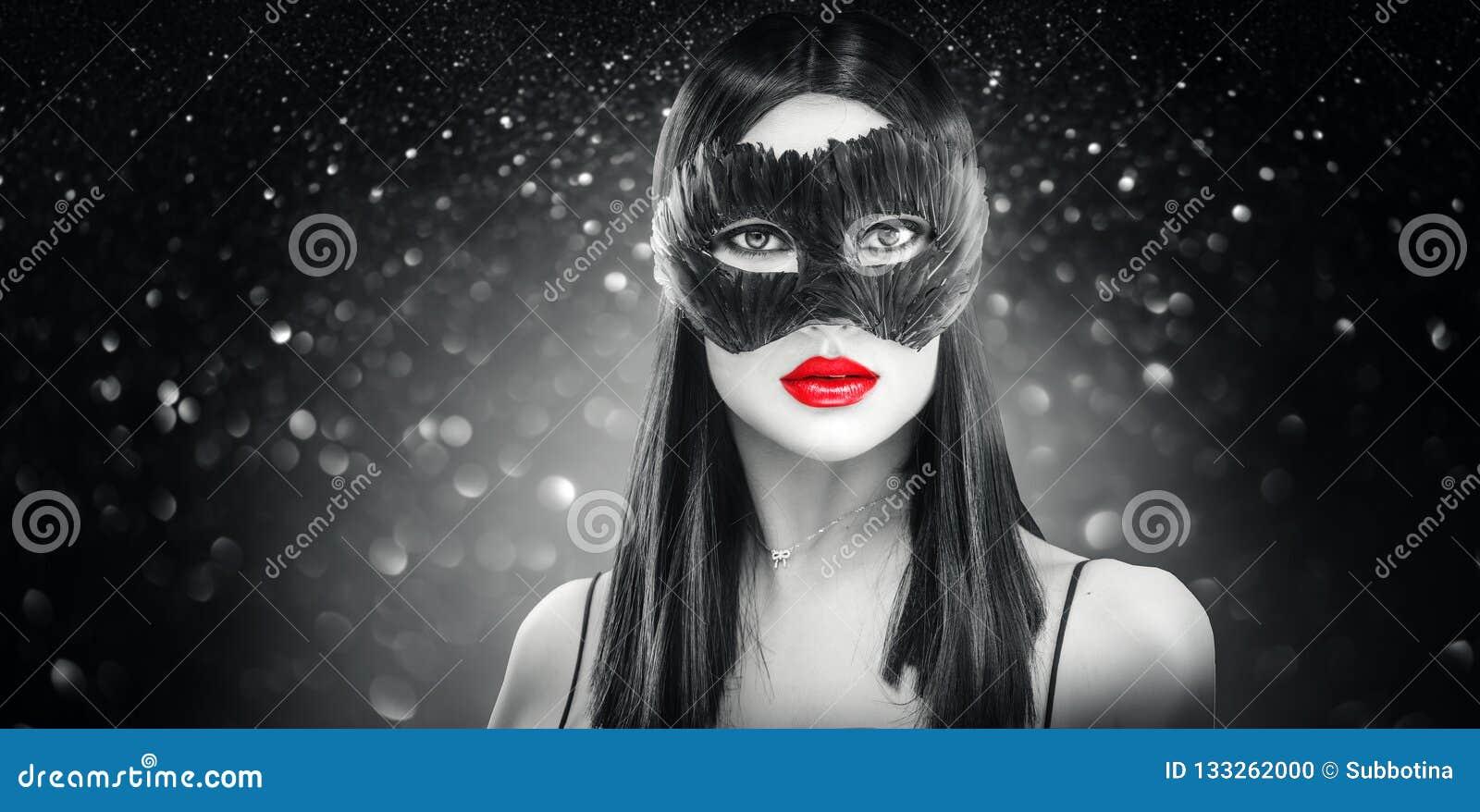 Γυναίκα brunette γοητείας ομορφιάς που φορά τη σκοτεινή μάσκα φτερών καρναβαλιού, κόμμα πέρα από το μαύρο υπόβαθρο διακοπών