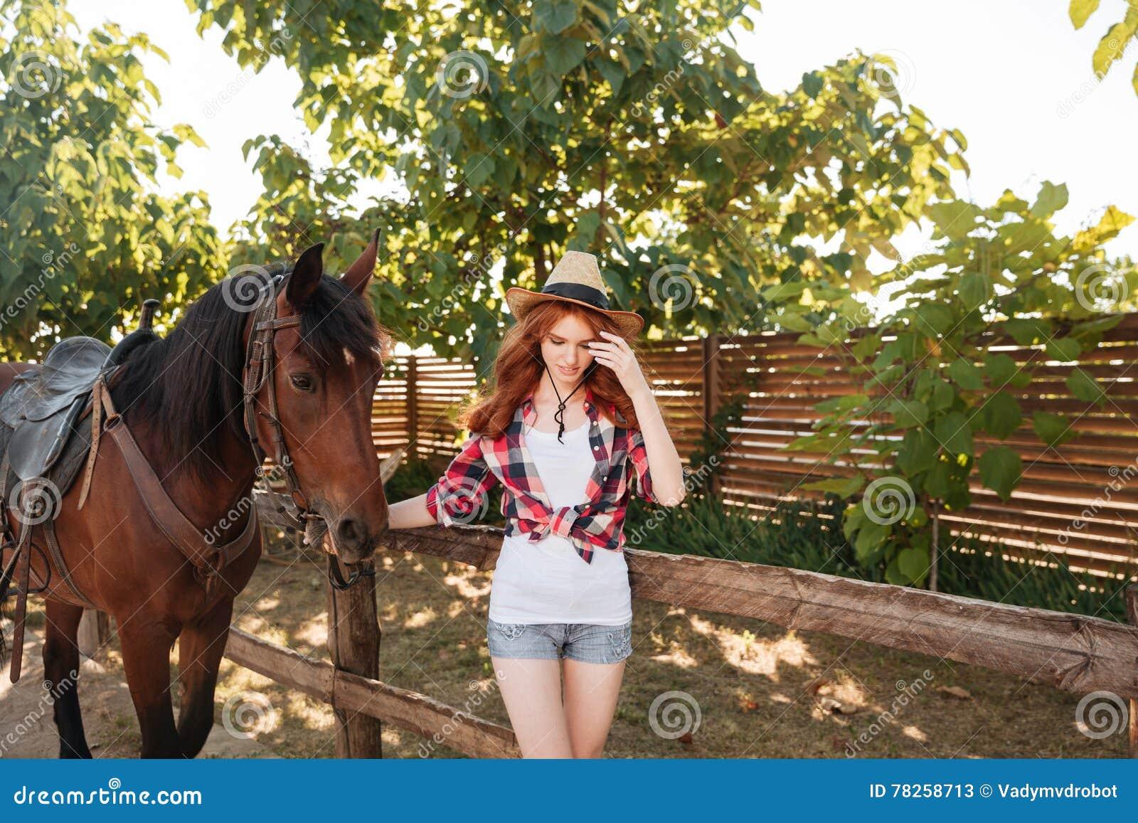 Γυναίκα cowgirl που περπατά με το άλογό της στο χωριό