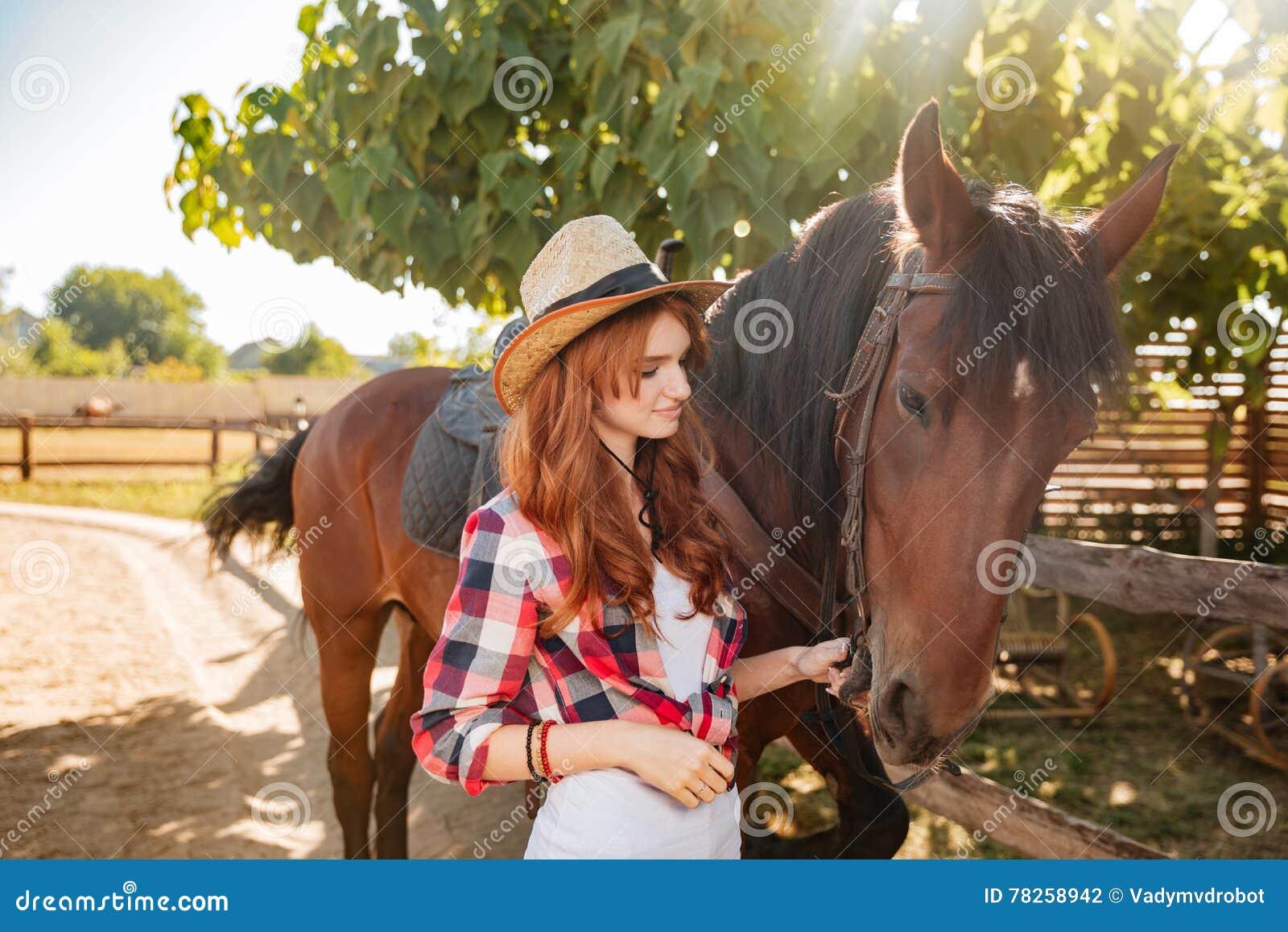 Γυναίκα cowgirl που στέκεται και που φροντίζει το άλογο στο χωριό