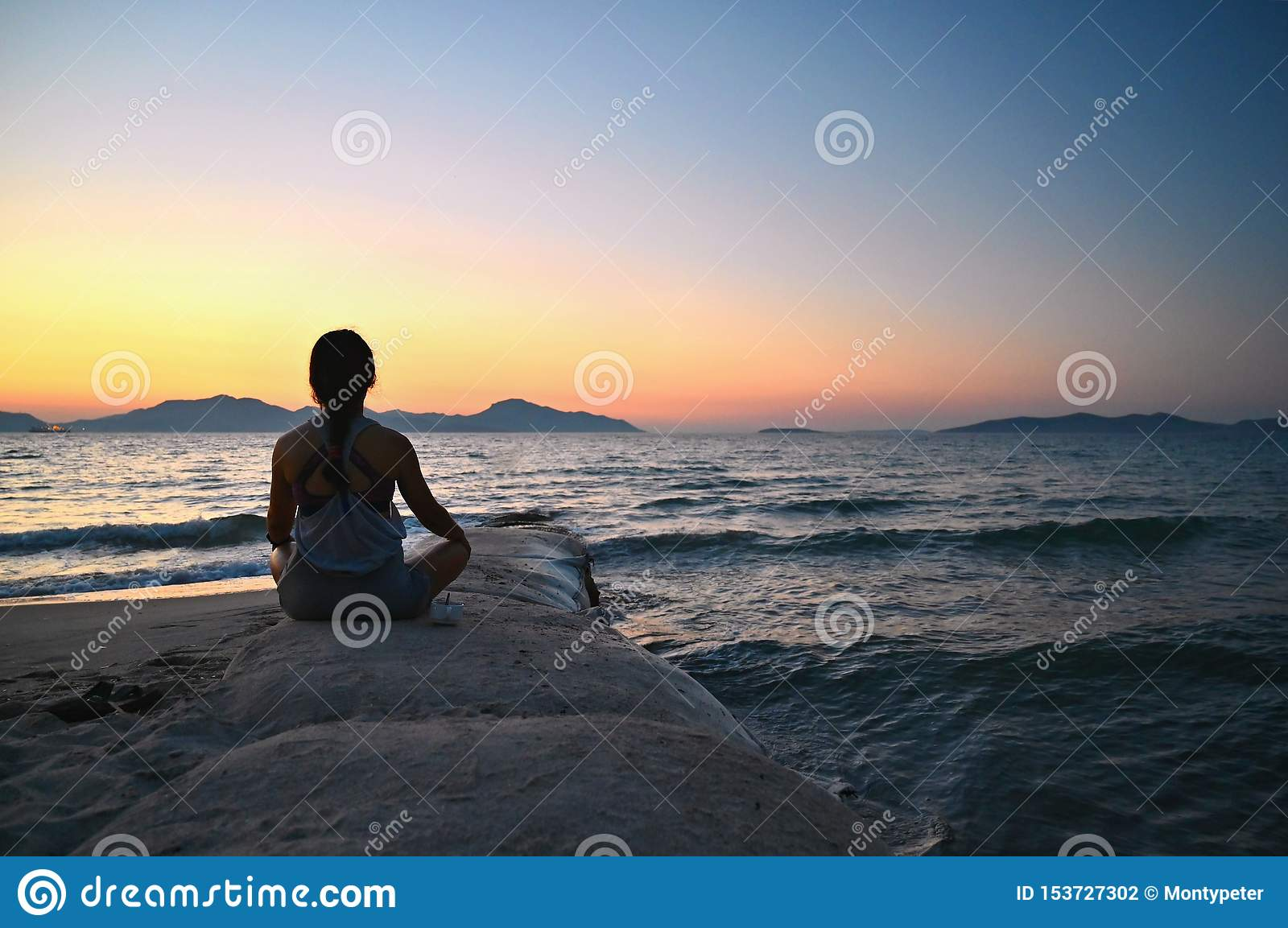 Γυναίκα meditates - χαλαρώνει στο ηλιοβασίλεμα θαλασσίως στην παραλία Έννοια για τη γιόγκα, την υγεία και τη SPA