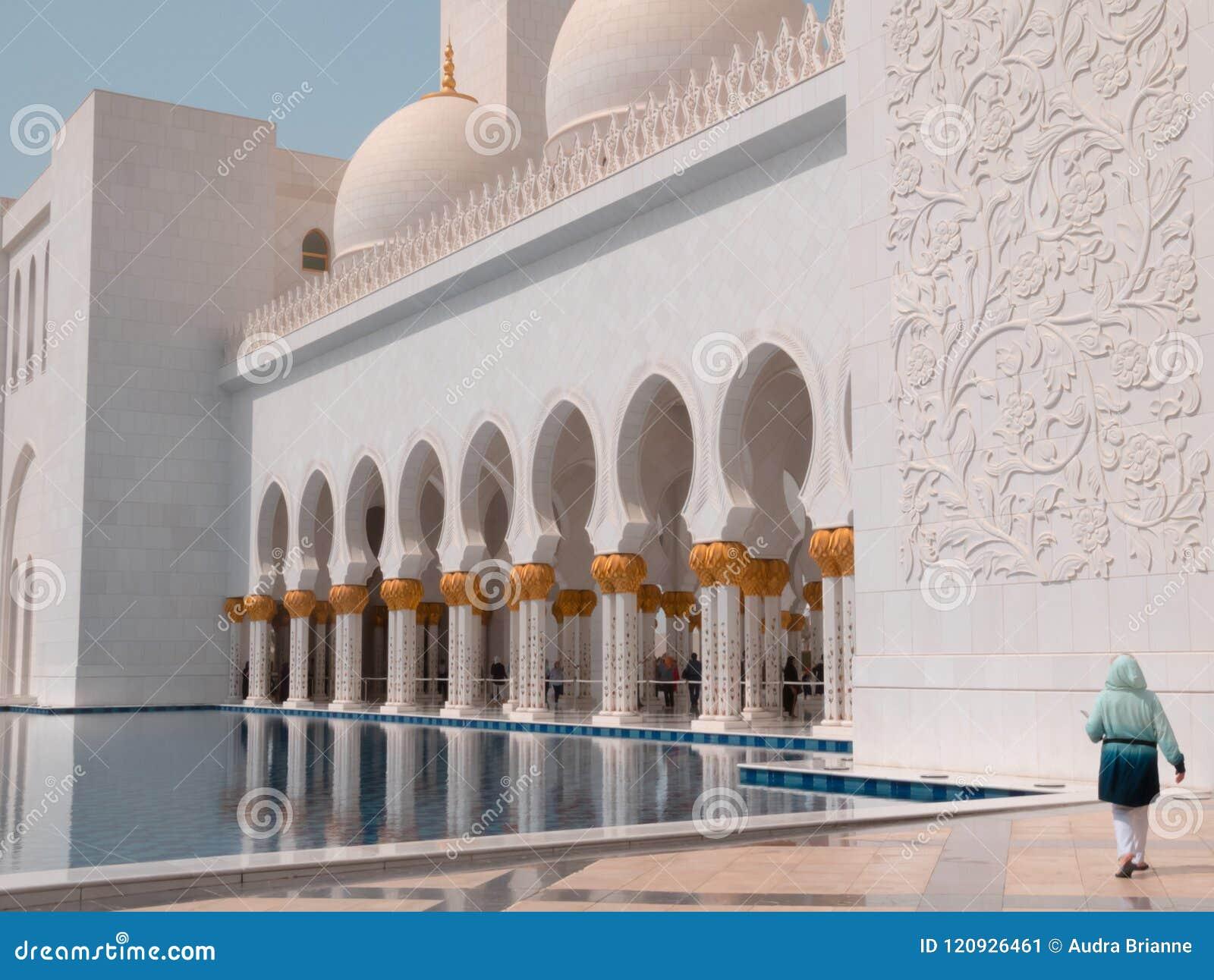 Γυναίκα Sheikh στο μεγάλο μουσουλμανικό τέμενος Zayed στο Αμπού Ντάμπι, Ε.Α.Ε. στη λίμνη αντανάκλασης