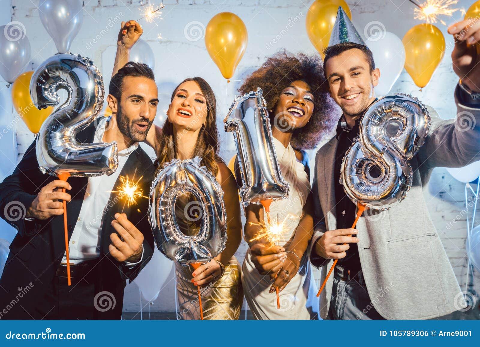 Γυναίκες και άνδρες ανθρώπων κόμματος που γιορτάζουν τη νέα παραμονή 2018 ετών