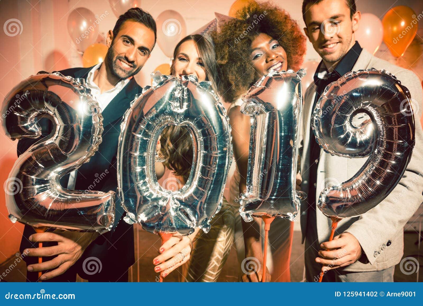 Γυναίκες και άνδρες ανθρώπων κόμματος που γιορτάζουν τη νέα παραμονή 2019 ετών