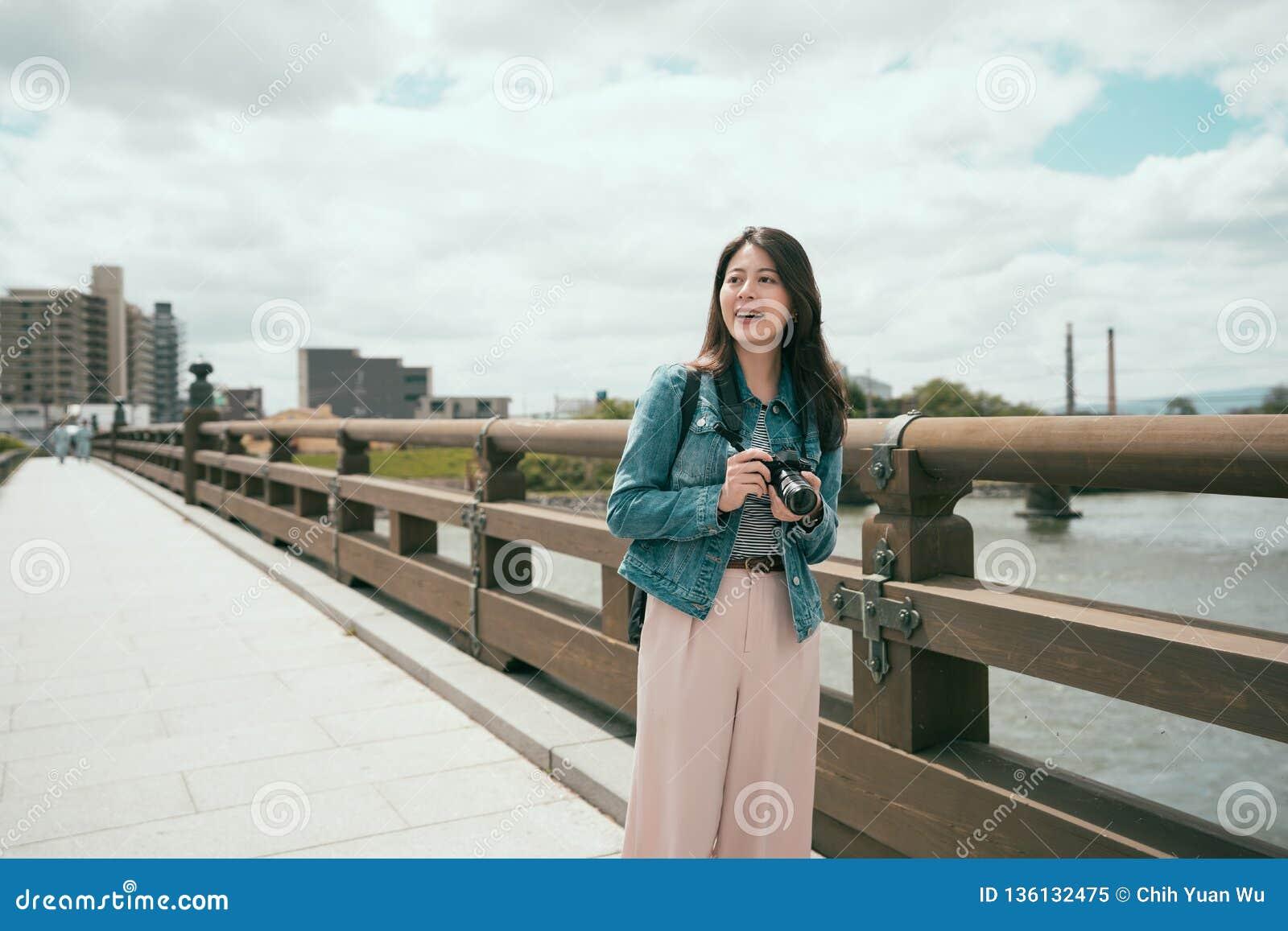 Γυναικείος περίπατος που διασχίζει τη γέφυρα επάνω από τον ποταμό