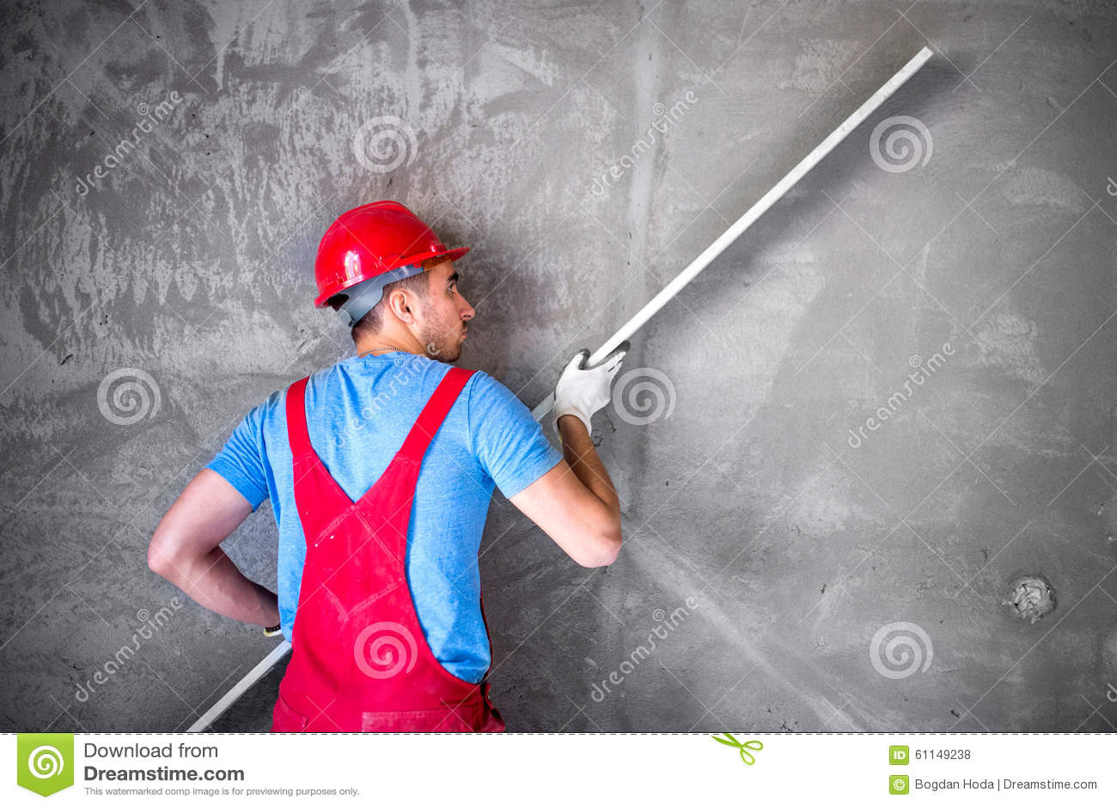 Γυψαδόρος στην εργασία για το εργοτάξιο οικοδομής, τους ισοπεδώνοντας τοίχους και τον έλεγχο της ποιότητας Βιομηχανικός εργάτης σ