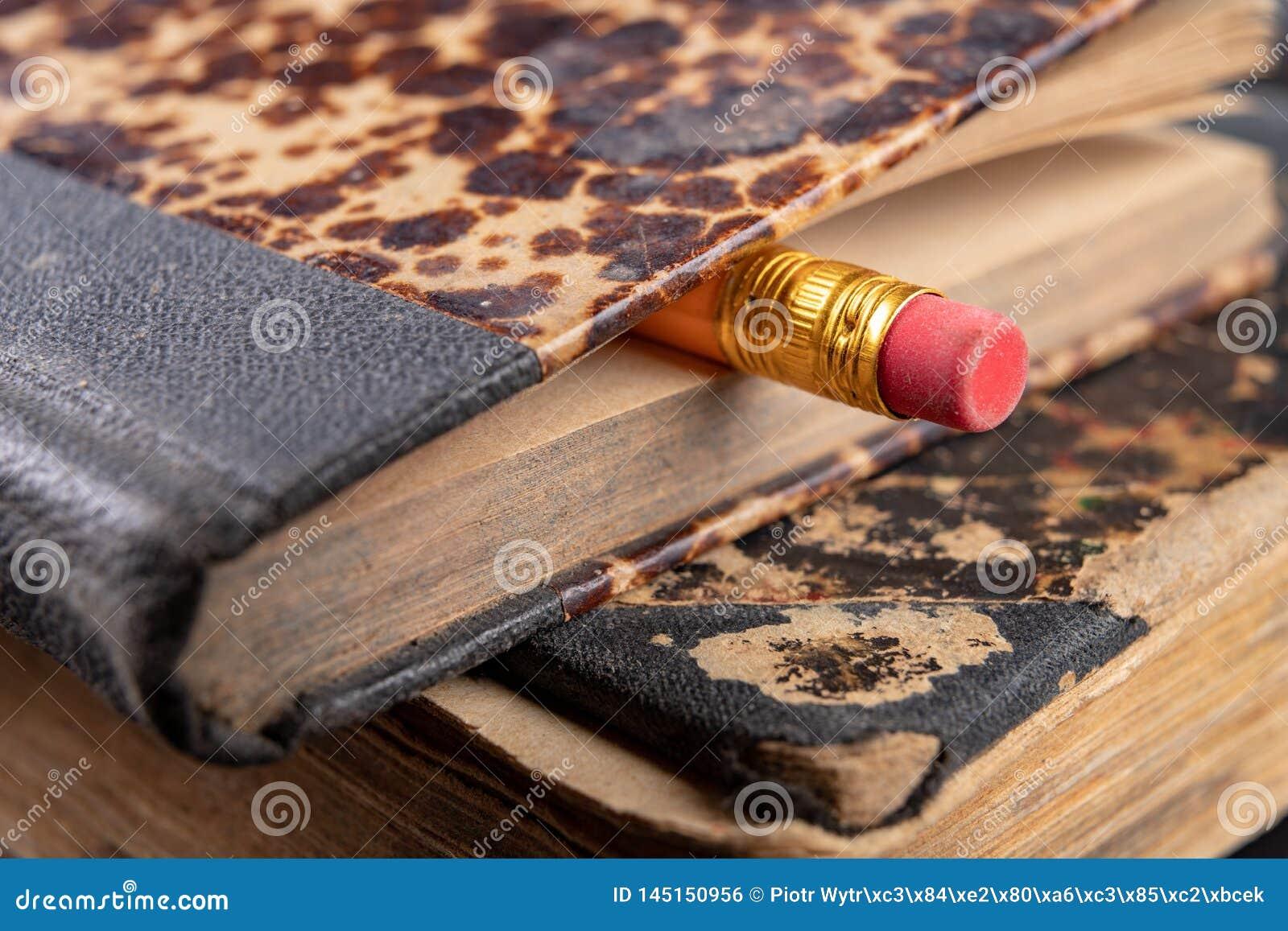 Γόμα που δεσμεύεται σε ένα μολύβι και ένα παλαιό βιβλίο Γράφοντας εξαρτήματα και βιβλία σε έναν παλαιό πίνακα