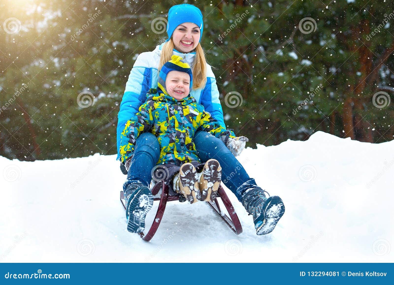 Γύρος μητέρων και γιων στο έλκηθρο Παιδικό παιχνίδι στη χιονώδη δασική υπαίθρια χειμερινή διασκέδαση για τις διακοπές οικογενειακ