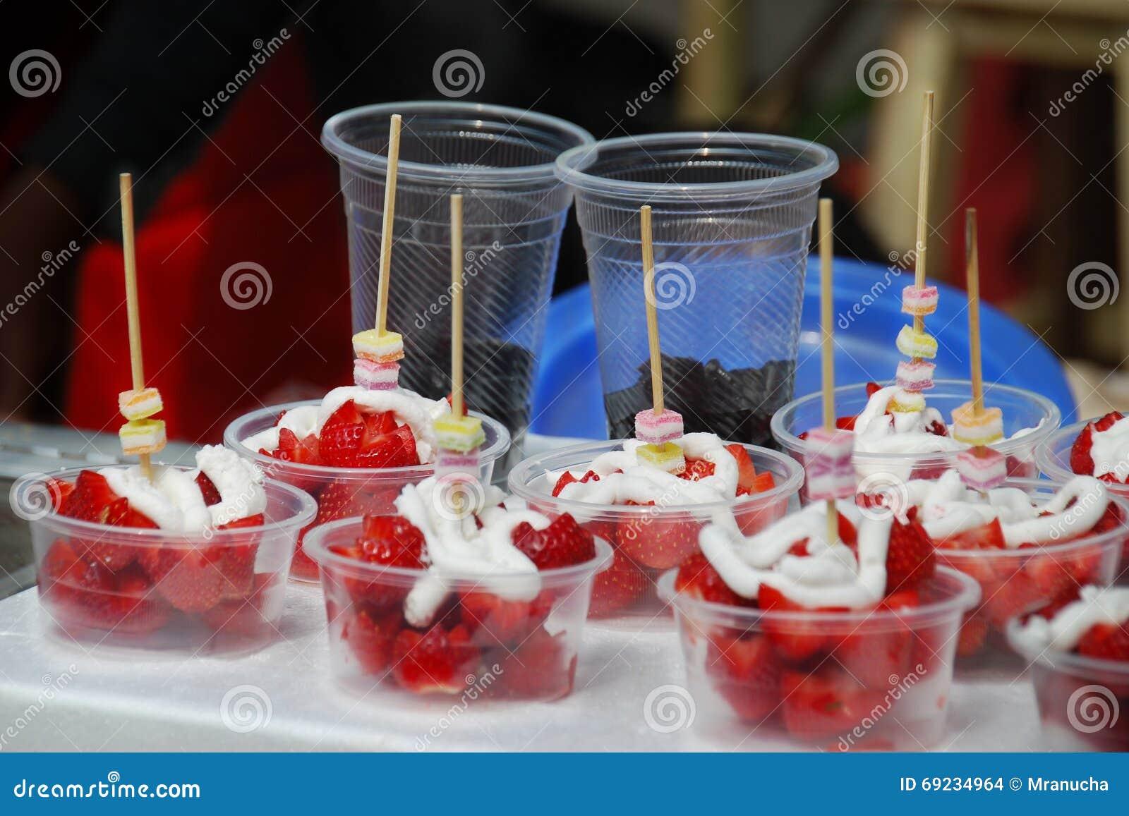 Γλυκό επιδόρπιο, φρέσκια φράουλα και ζωηρόχρωμη ζελατίνα με το κτυπημένο κάλυμμα κρέμας