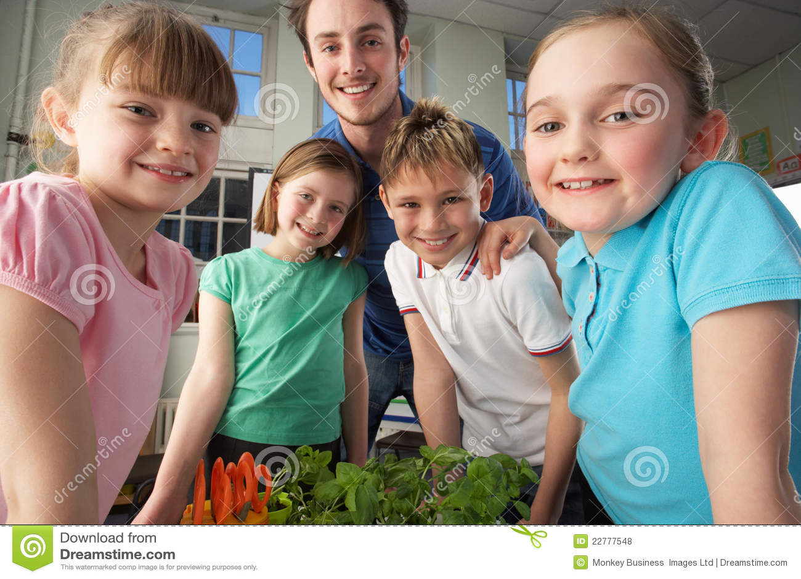Δάσκαλος με τα παιδιά που μαθαίνουν για τα φυτά