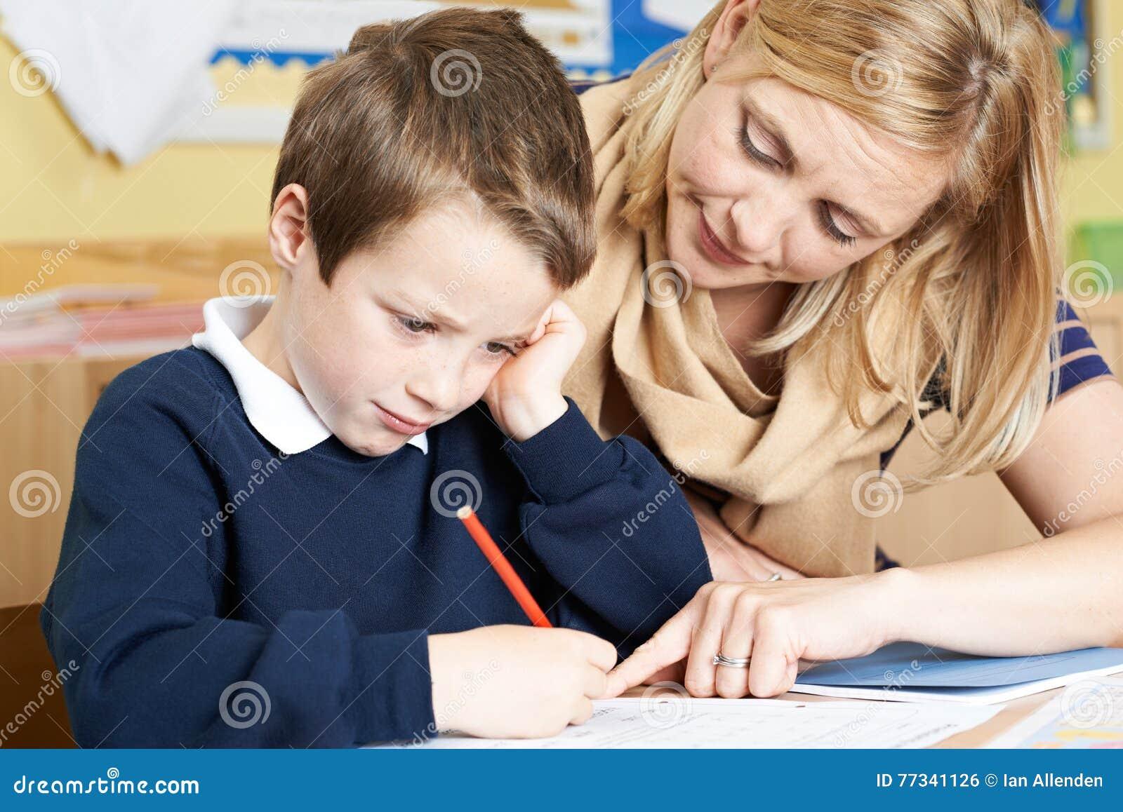 Δάσκαλος που βοηθά τον αρσενικό μαθητή δημοτικού σχολείου με το πρόβλημα