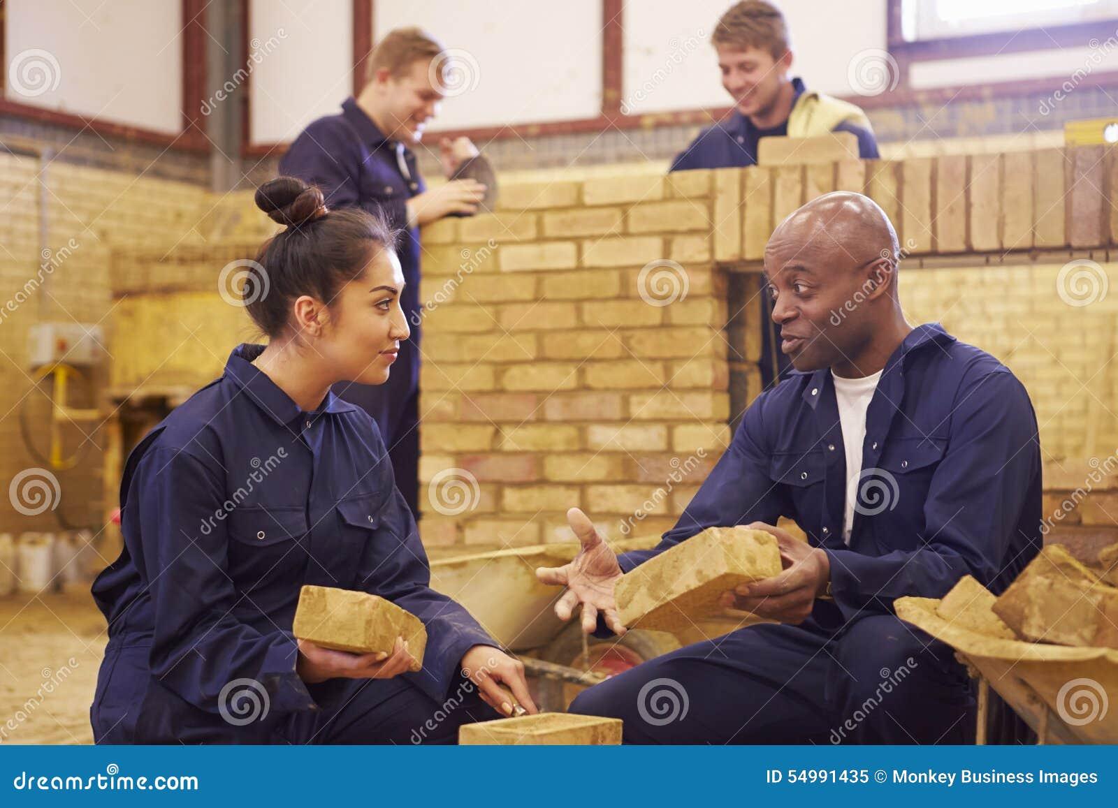 Δάσκαλος που βοηθά τους σπουδαστές που εκπαιδεύουν να είναι οικοδόμοι