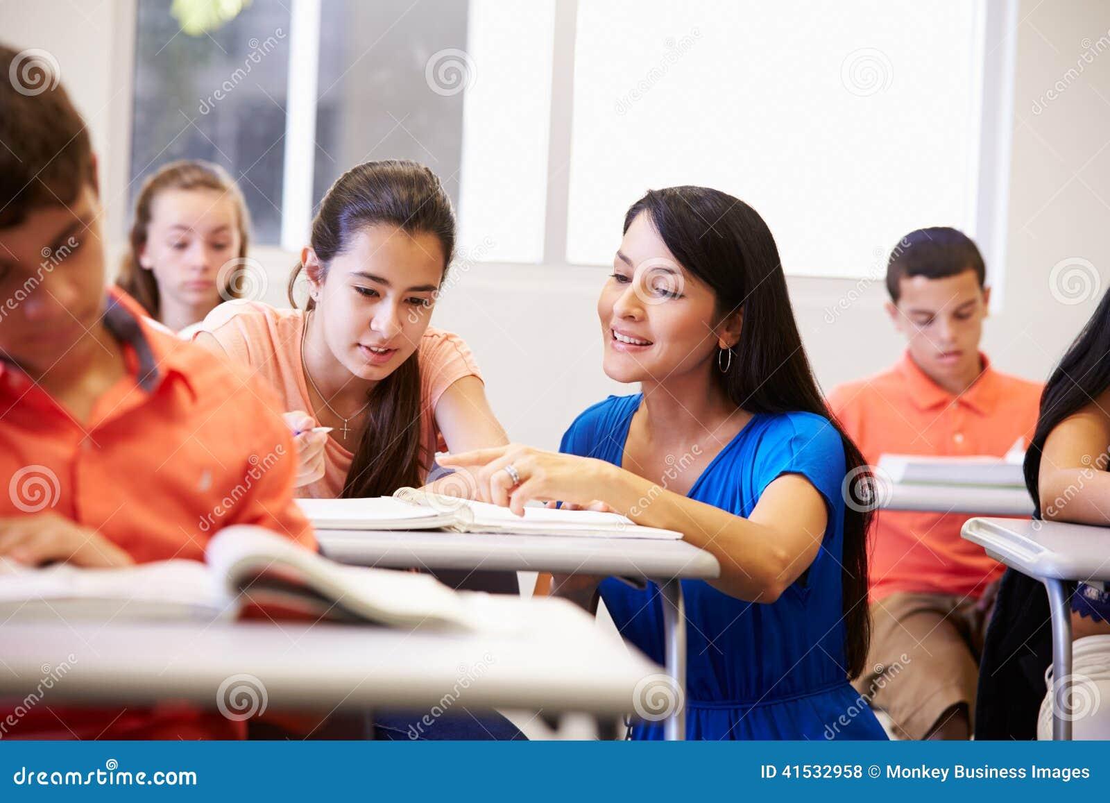 Δάσκαλος που βοηθά το θηλυκό σπουδαστή γυμνασίου στην τάξη