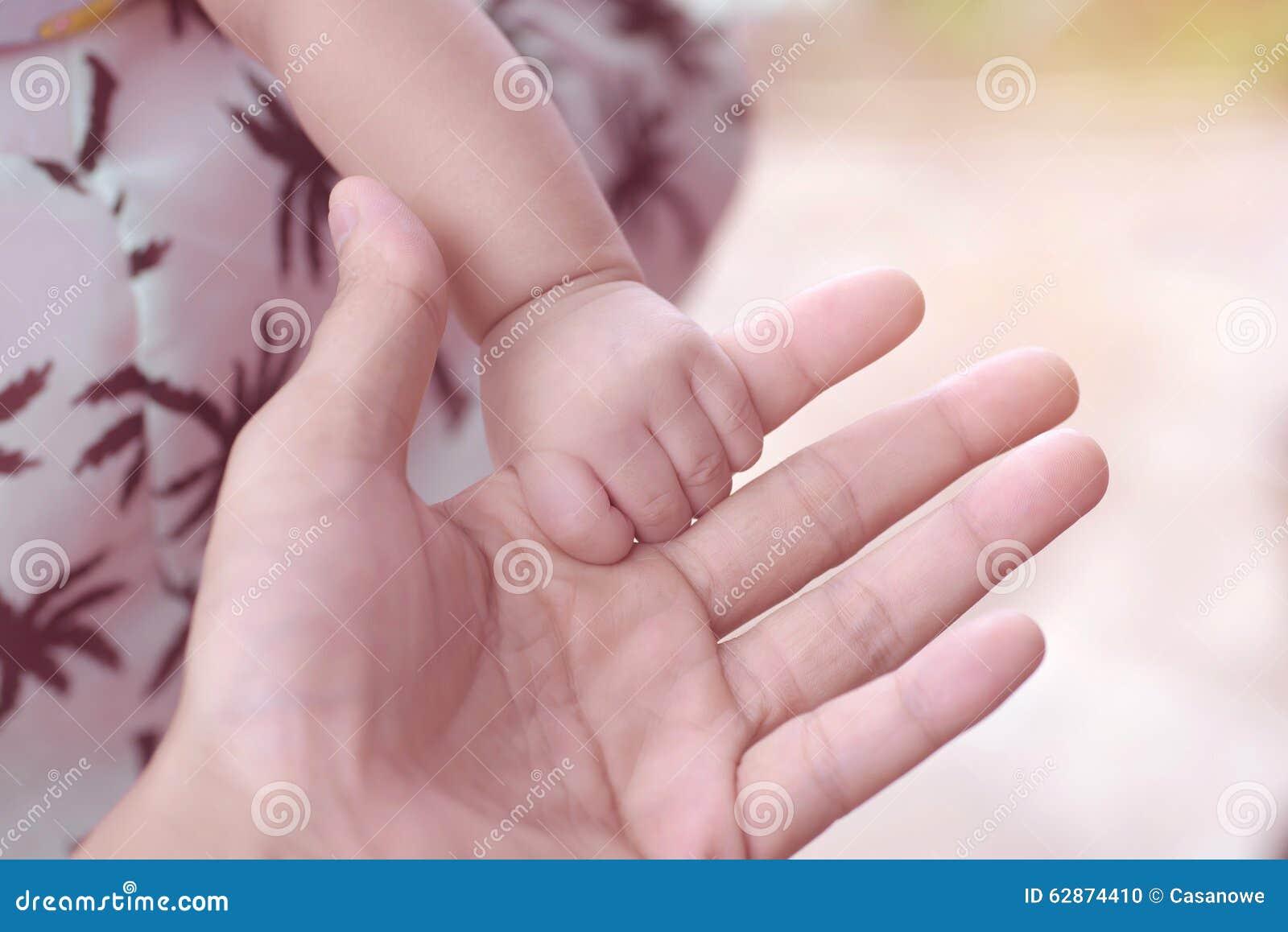 Δάχτυλο της χαριτωμένης νεογέννητης μωρών χεριών μητέρας εκμετάλλευσης