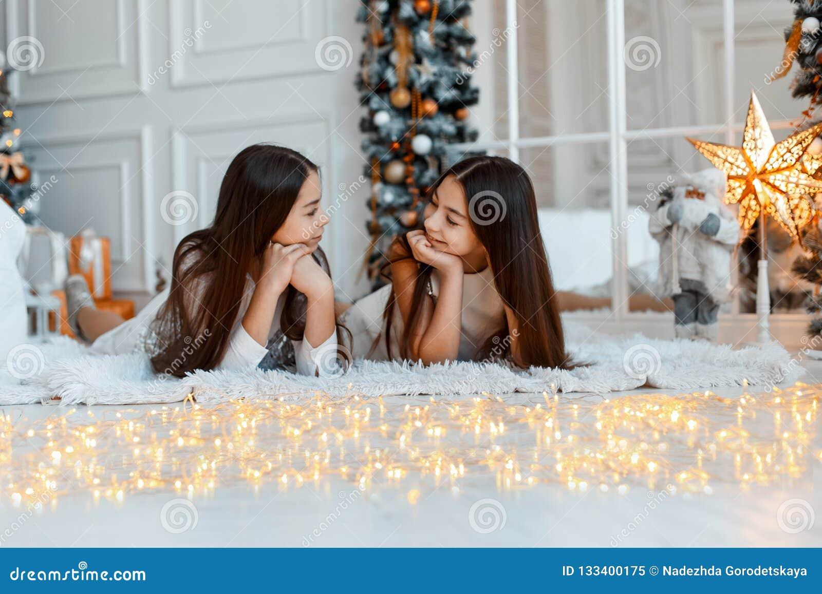 Δίδυμα κοριτσιών μπροστά από fir-tree Νέα παραμονή έτους ` s Χριστούγεννα Άνετες διακοπές fir-tree με τα φω τα