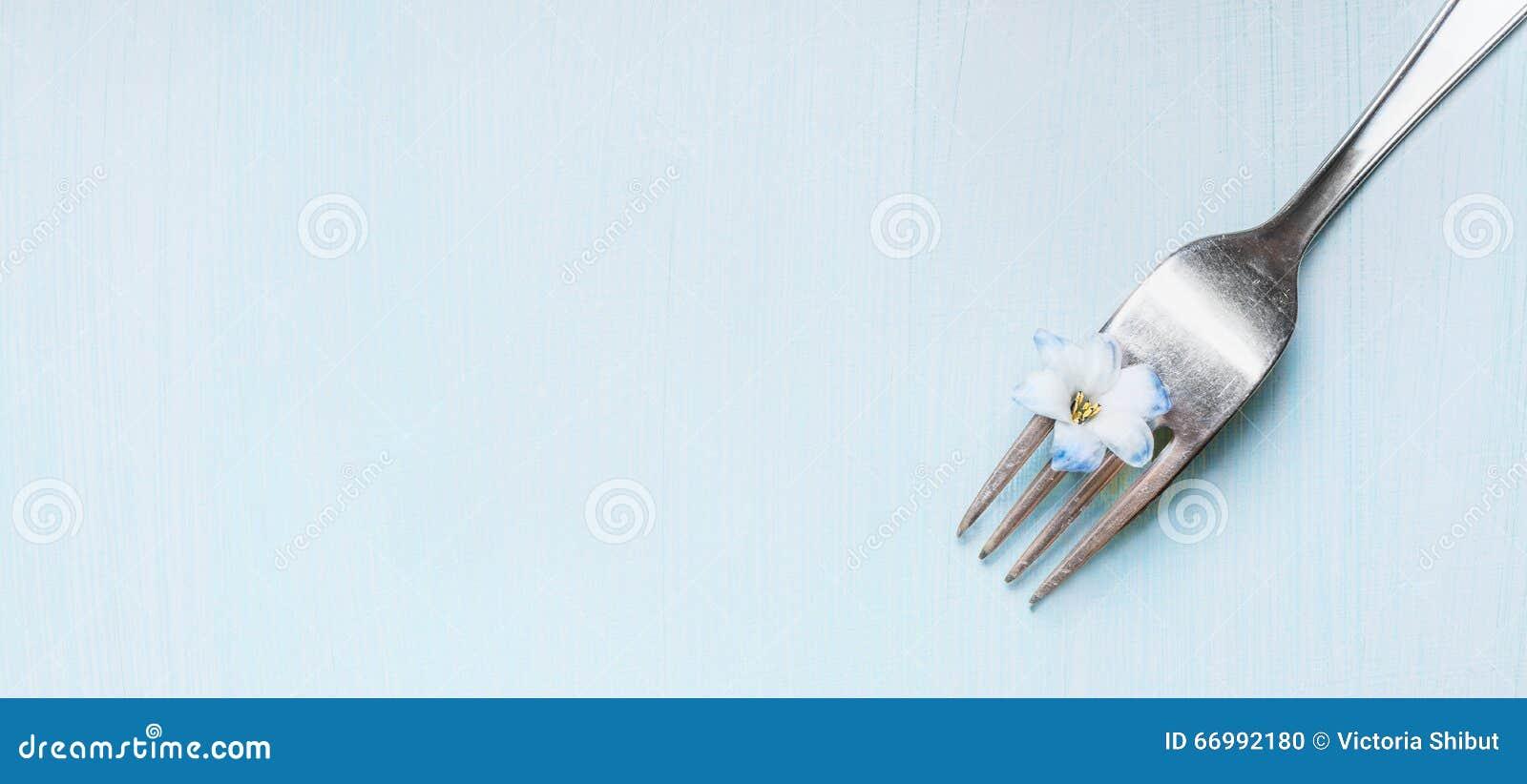 Δίκρανο με λίγο μπλε λουλούδι στο ανοικτό πράσινο shabby αγροτικό υπόβαθρο, τοπ άποψη