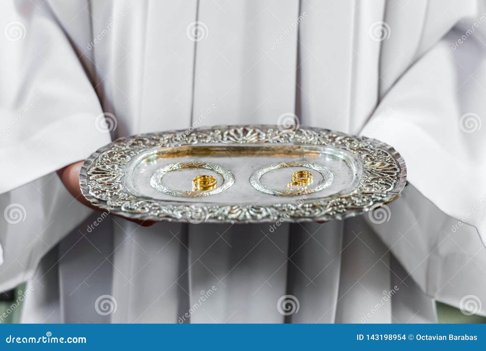 Δαχτυλίδια ιερέων και γάμου στην ασημένια πιατέλα