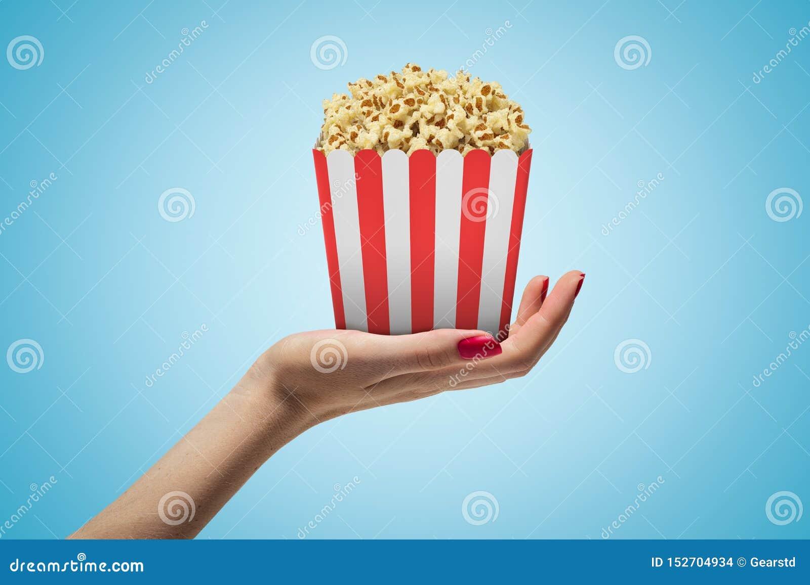 Δευτερεύουσα κινηματογράφηση σε πρώτο πλάνο του χεριού της γυναίκας που αντιμετωπίζει επάνω και που κρατά το ριγωτό popcorn κιβώτ