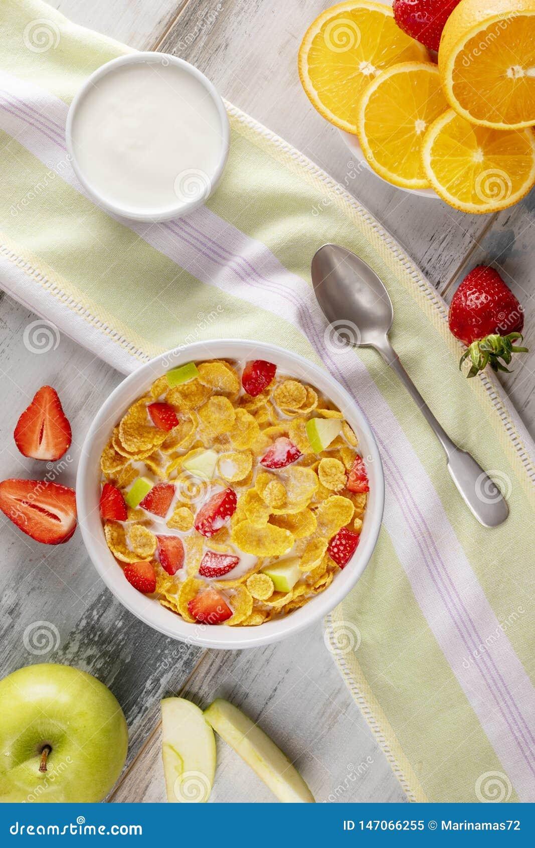 Δημητριακά και φράουλες προγευμάτων με το γάλα, το γιαούρτι και το χυμό από πορτοκάλι