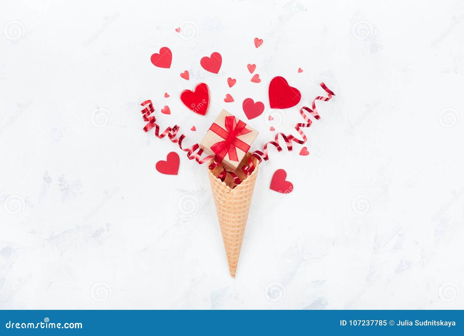 Δημιουργική σύνθεση για την ημέρα βαλεντίνων με τον κώνο βαφλών, το δώρο ή το παρούσες κιβώτιο και τις καρδιές στην άσπρη τοπ άπο