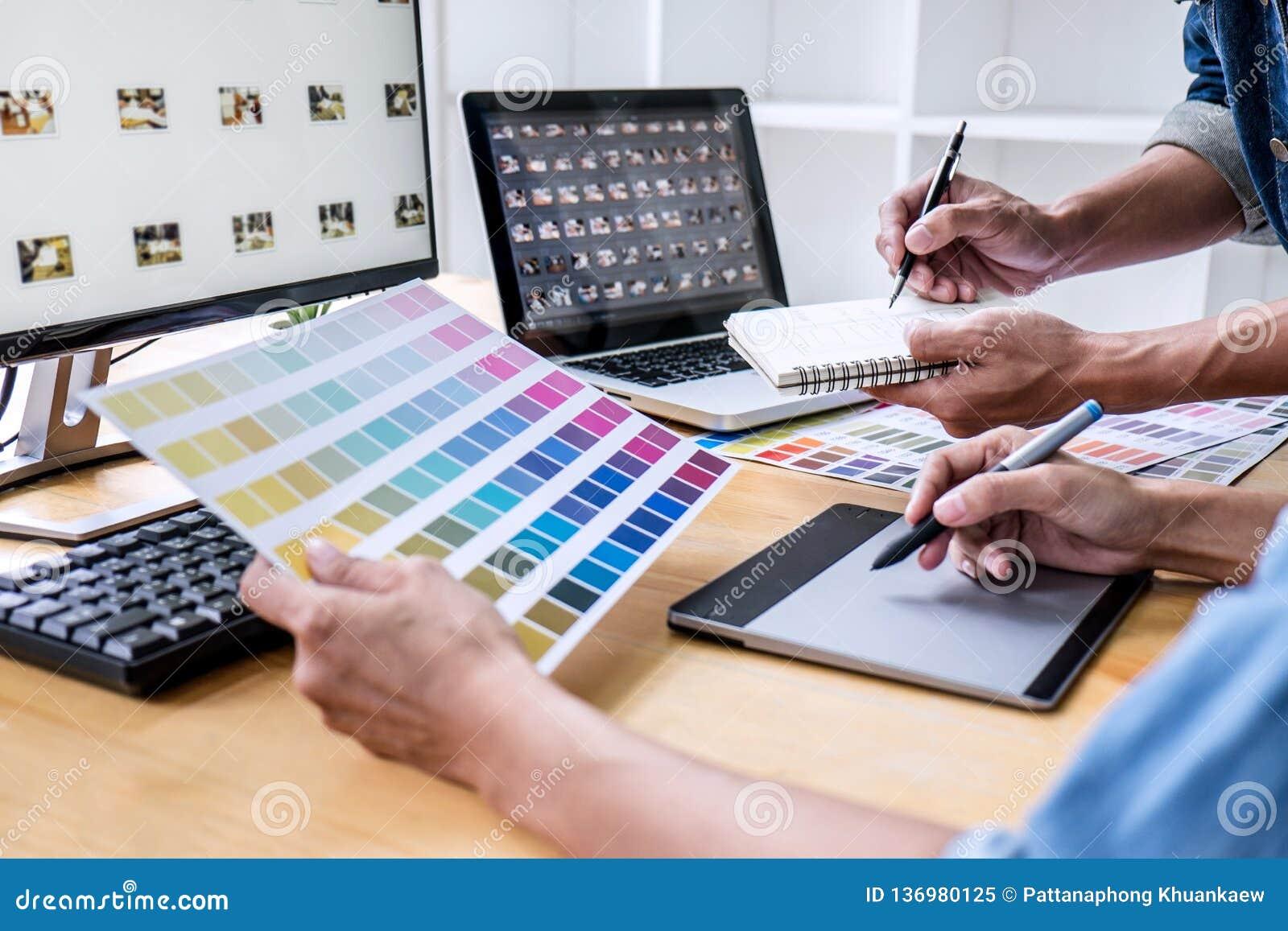 Δημιουργικός γραφικός σχεδιαστής δύο συναδέλφων που εργάζεται στην επιλογή χρώματος και που επισύρει την προσοχή στην ταμπλέτα γρ