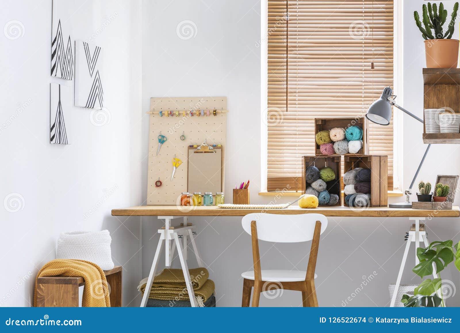 Δημιουργικός χώρος εργασίας με τα Σκανδιναβικά, ξύλινα έπιπλα, τους άσπρους τοίχους και τα ράβοντας εργαλεία σε ένα σύγχρονο εσωτ
