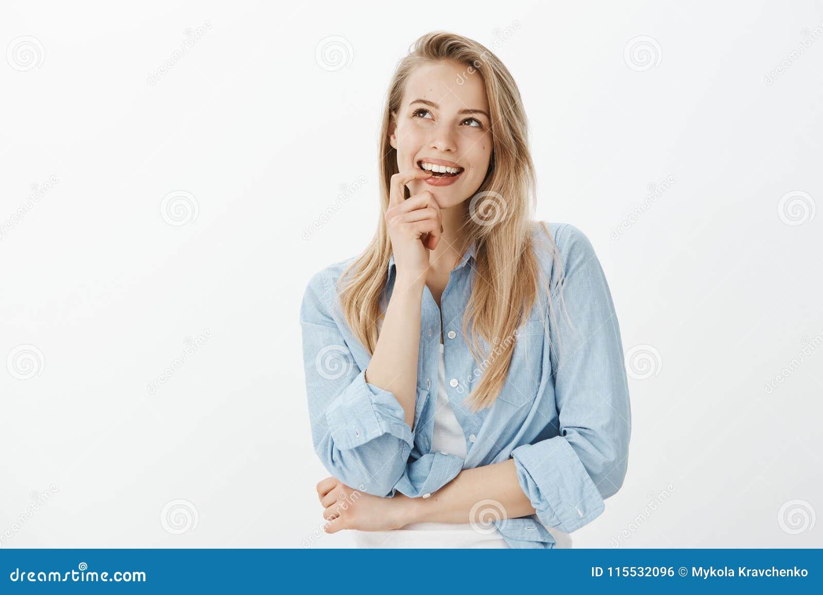 Δημιουργικός όμορφος θηλυκός σχεδιαστής με τα ξανθά μαλλιά, δάχτυλο δαγκώματος, να φανεί επάνω και να χαμογελάσει περίεργα ενώ έχ