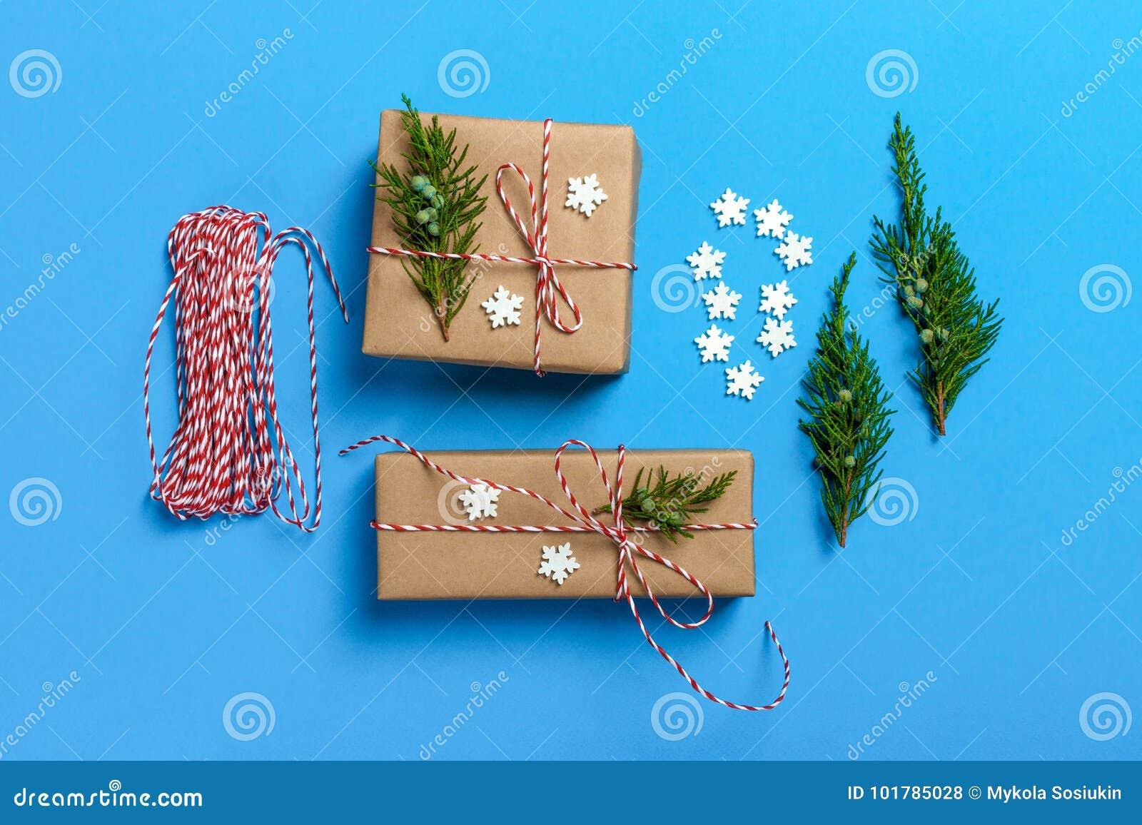 Δημιουργικό χόμπι Τύλιγμα δώρων Συσκευασία των σύγχρονων κιβωτίων χριστουγεννιάτικου δώρου στο μοντέρνο γκρίζο έγγραφο με την κόκ