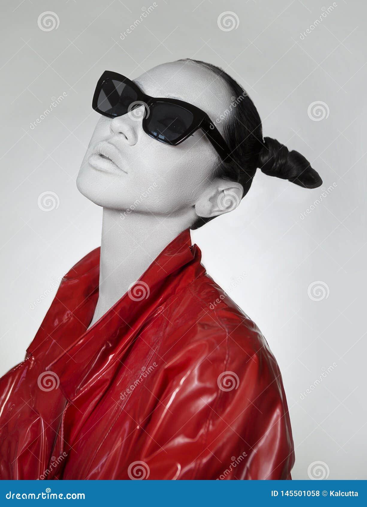 Δημιουργικό glamor Νέα γυναίκα στο μοντέρνα κόκκινα μακριά αδιάβροχο και τα γυαλιά ηλίου λάκκας