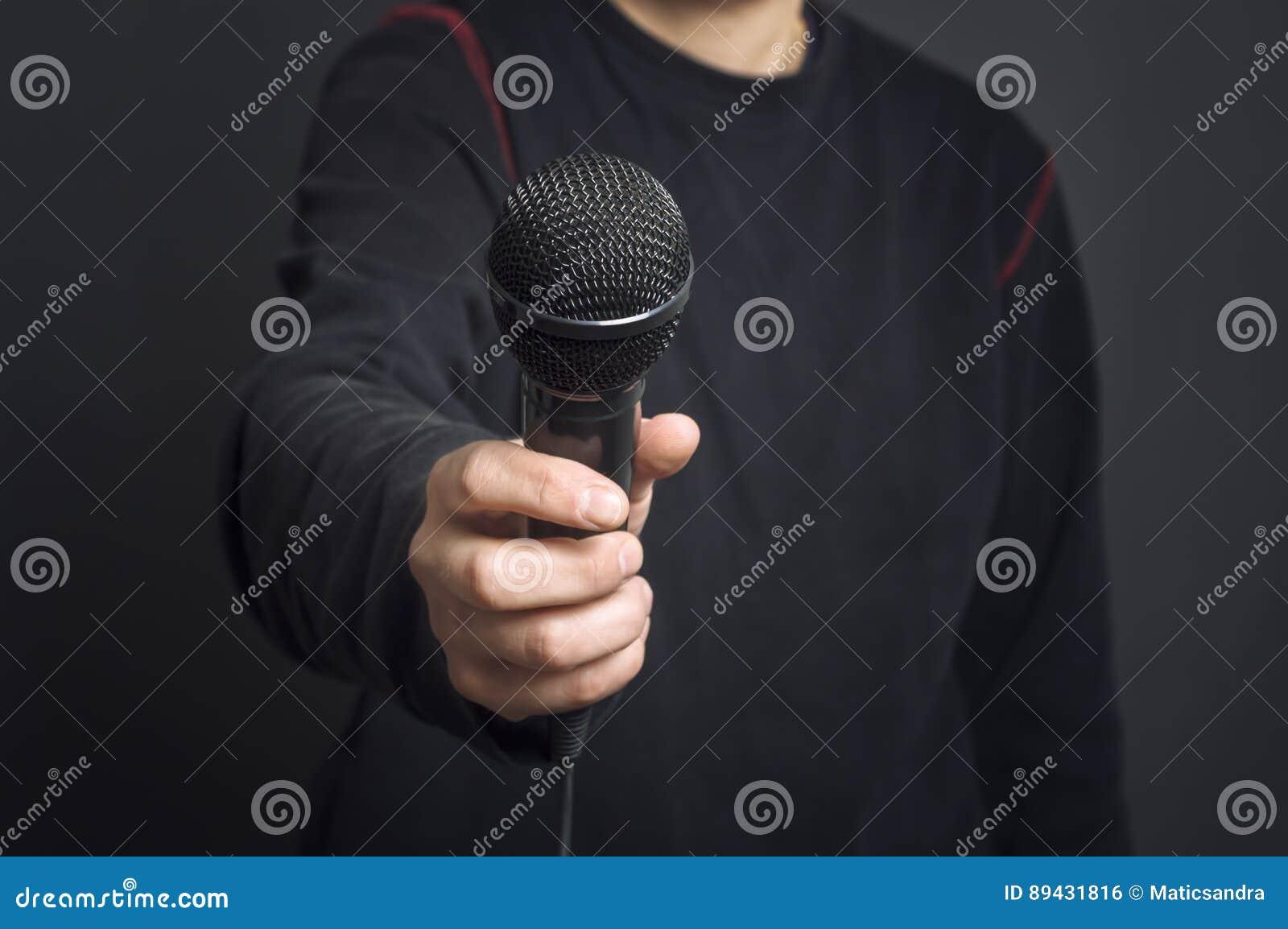 Δημοσιογράφος που κάνει την ομιλία με τη gesturing έννοια μικροφώνων και χεριών για τη συνέντευξη