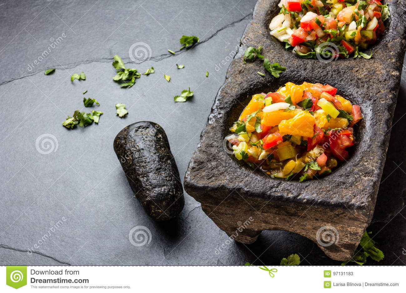 Διάσημα μεξικάνικα salsas σαλτσών - pico de Gallo, mexicana bandera salsa στα κονιάματα πετρών στο γκρίζο υπόβαθρο πλακών