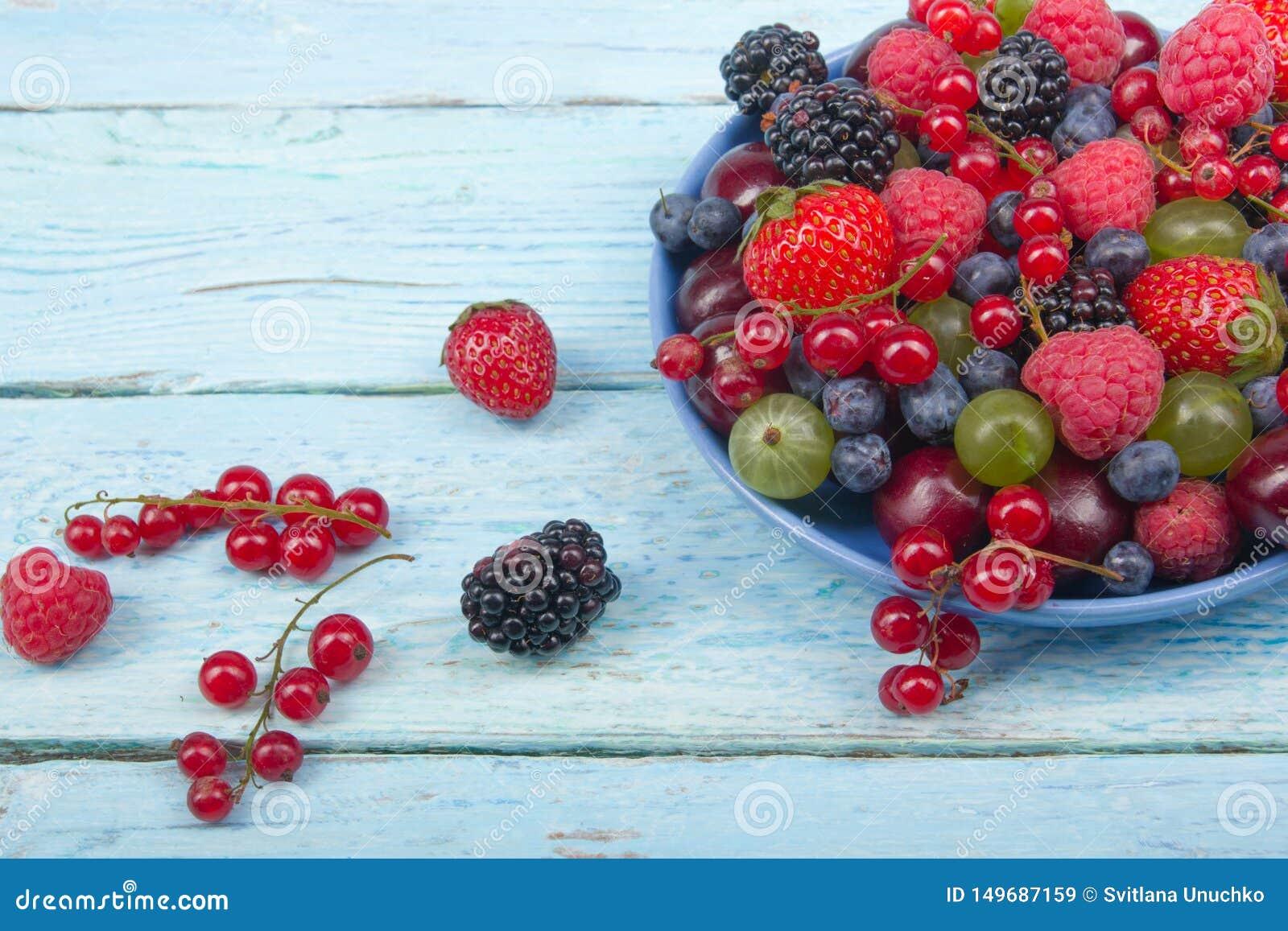 Διάφορα θερινά φρέσκα μούρα σε ένα κύπελλο στον αγροτικό ξύλινο πίνακα Αντιοξειδωτικοοι, detox διατροφή, οργανικά φρούτα