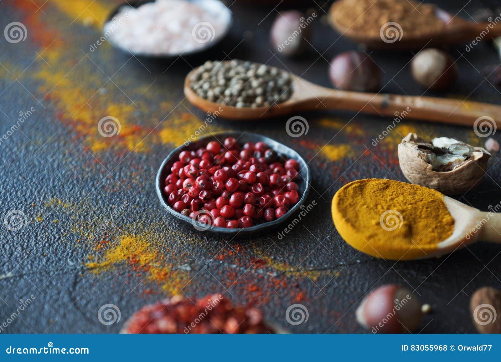 Διάφορα ινδικά καρυκεύματα στα ξύλινα κουτάλια και τα κύπελλα μετάλλων και καρύδια στο σκοτεινό πίνακα πετρών Ζωηρόχρωμα καρυκεύμ