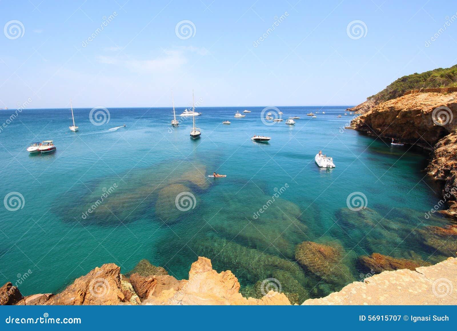 Διάφορες βάρκες πλέουν μέσω των νερών κρυστάλλου κοντά στο όμορφες χωριό και την παραλία Sa Riera