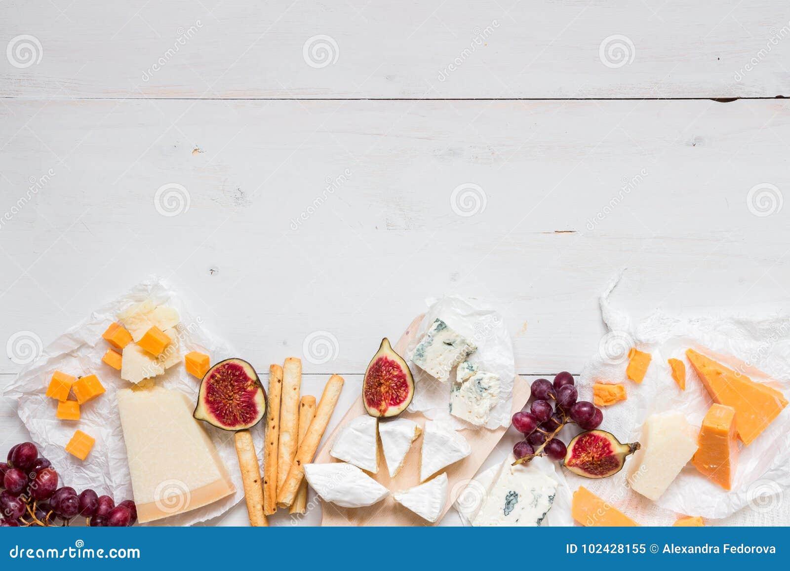 Διάφοροι τύποι τυριών με τα φρούτα στον ξύλινο άσπρο πίνακα με το διάστημα αντιγράφων Τοπ όψη