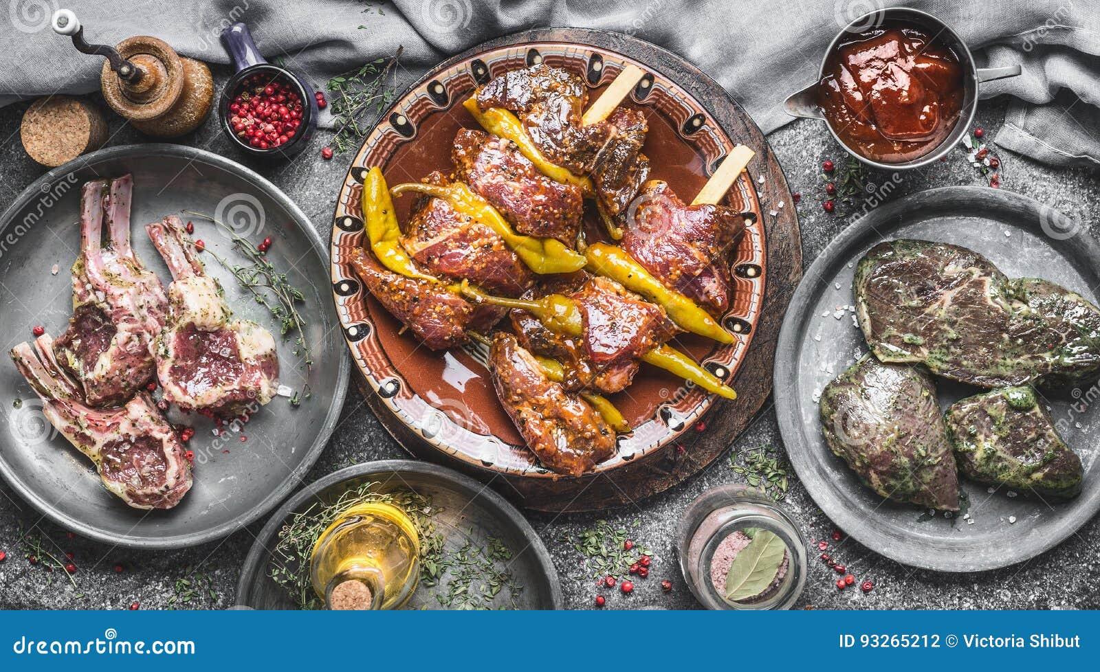 Διάφορο κρέας για τη σχάρα: τα οβελίδια κρέατος, τα πλευρά ραφιών αρνιών και οι μαριναρισμένες μπριζόλες στην αγροτική κουζίνα πα