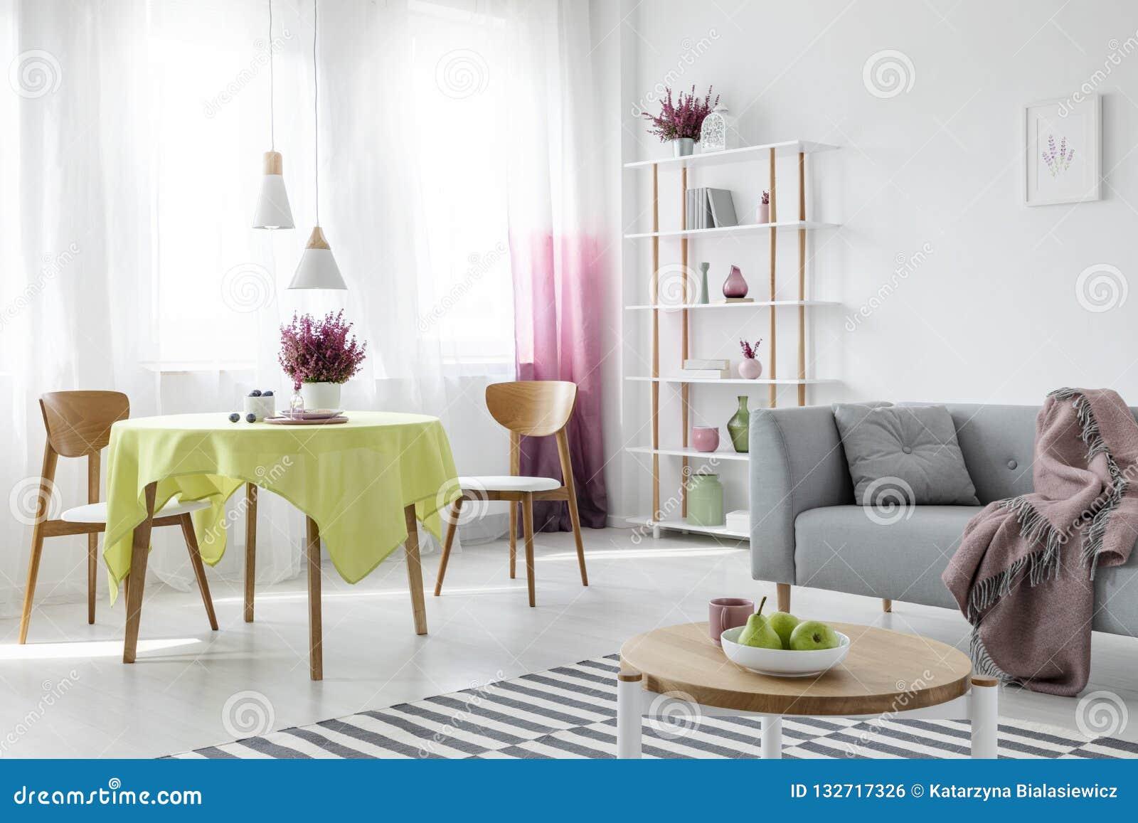Διαβίωση και τραπεζαρία στο διαμέρισμα με τον γκρίζο καναπέ και τα ξύλινα έπιπλα, πραγματική φωτογραφία