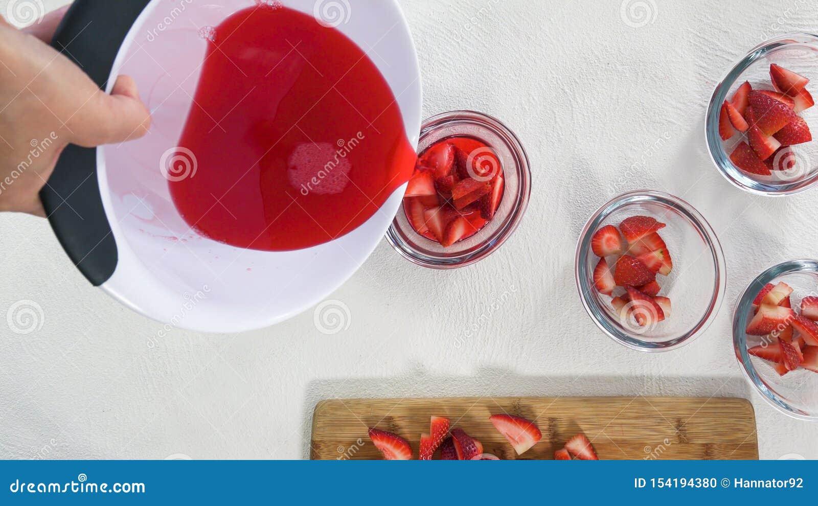 Διαδικασία προετοιμασιών ζελατίνας φραουλών Οι φέτες φραουλών σε ένα γυαλί κυλούν Χύνοντας μίγμα ζελατίνας κύπελλα Κλείστε επάνω