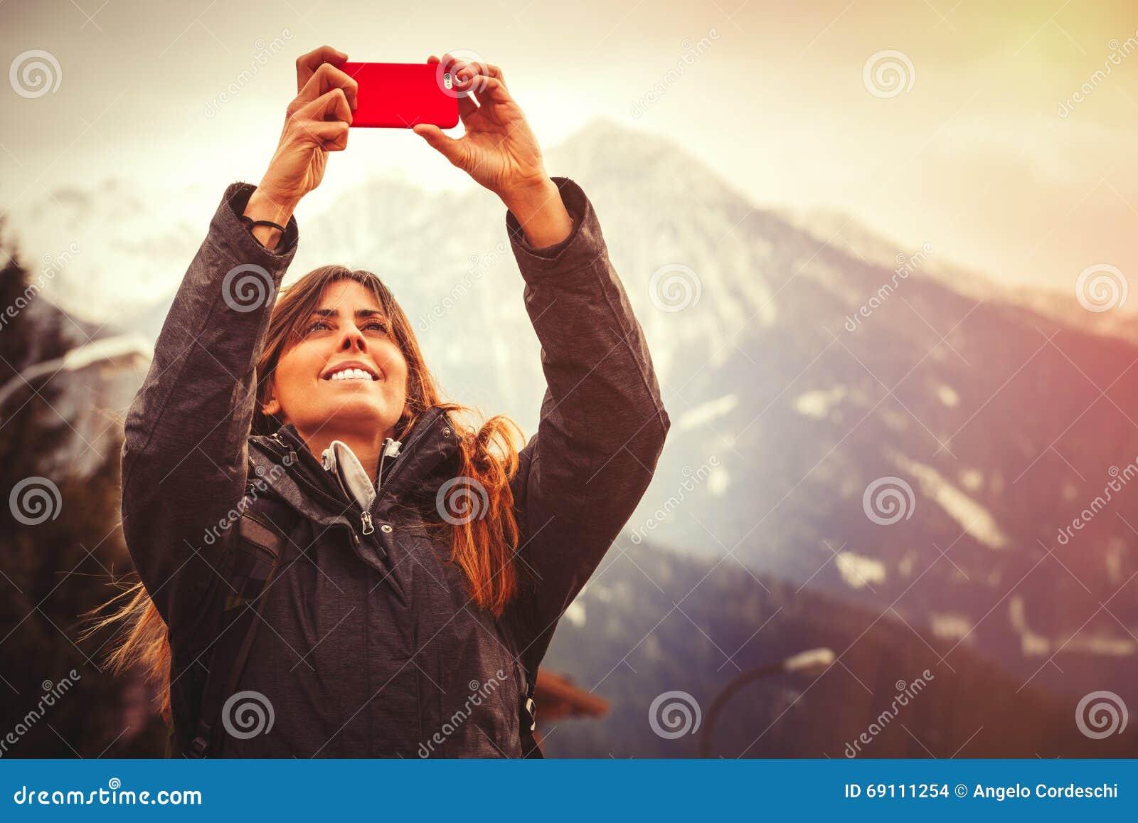 Διακοπές βουνών Ευτυχής γυναίκα που παίρνει μια εικόνα με ένα τηλέφωνο κυττάρων