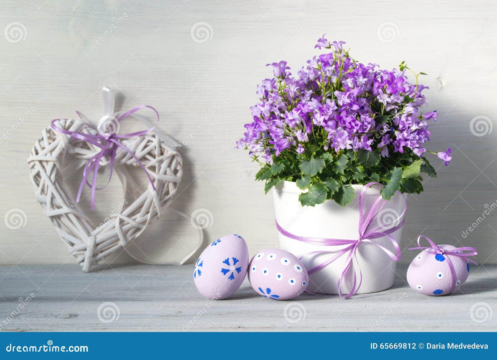 Διακοσμήσεις Πάσχας με τα αυγά Πάσχας, ένα δοχείο των πορφυρών λουλουδιών άνοιξη και καρδιά σε ένα άσπρο ξύλινο υπόβαθρο