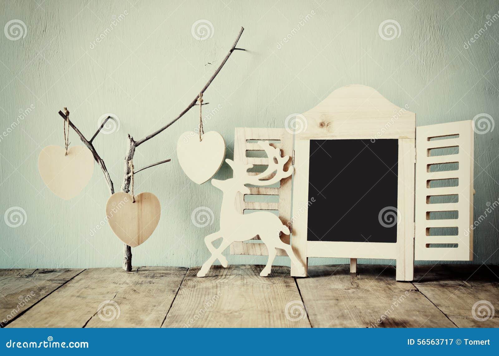 Download Διακοσμητικό πλαίσιο πινάκων κιμωλίας και ξύλινες κρεμώντας καρδιές πέρα από τον ξύλινο πίνακα έτοιμος για το κείμενο ή το πρότυπ Στοκ Εικόνα - εικόνα από κενός, καρδιά: 56563717
