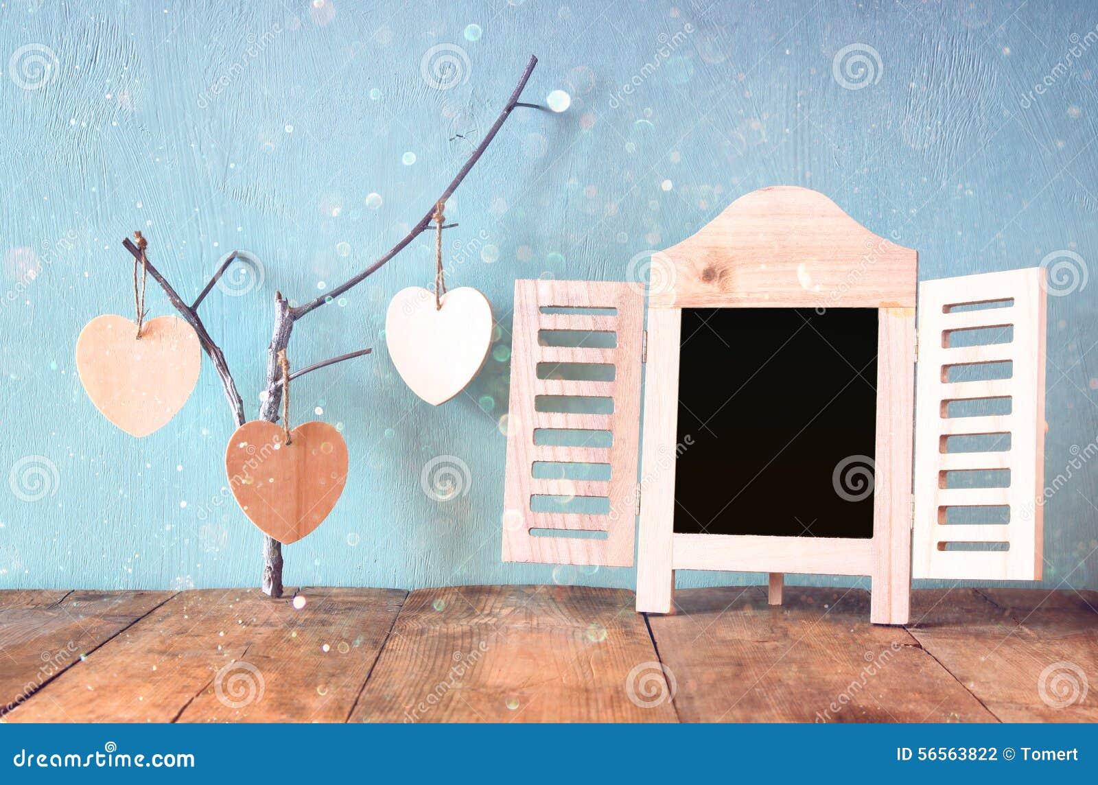 Download Διακοσμητικό πλαίσιο πινάκων κιμωλίας και ξύλινες κρεμώντας καρδιές πέρα από τον ξύλινο πίνακα έτοιμος για το κείμενο ή το πρότυπ Στοκ Εικόνες - εικόνα από ντεκόρ, μαύρα: 56563822