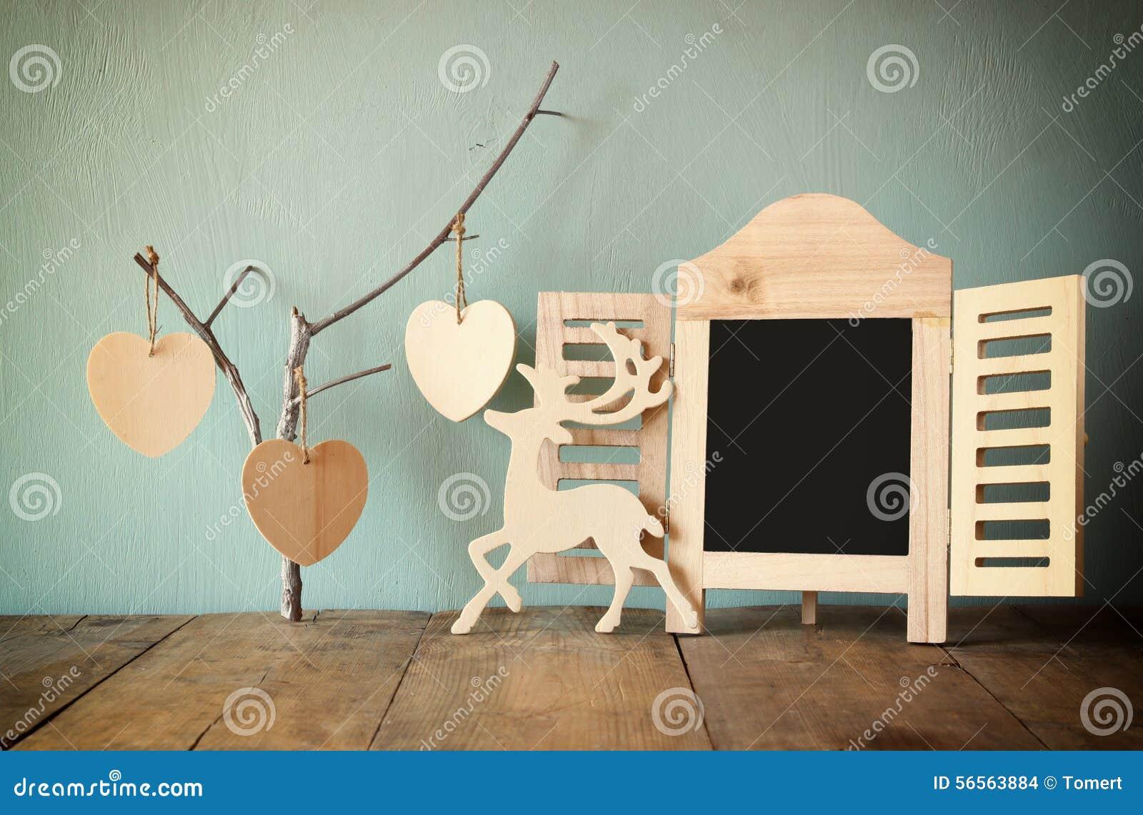 Download Διακοσμητικό πλαίσιο πινάκων κιμωλίας και ξύλινες κρεμώντας καρδιές πέρα από τον ξύλινο πίνακα έτοιμος για το κείμενο ή το πρότυπ Στοκ Εικόνες - εικόνα από ένωση, αγάπη: 56563884
