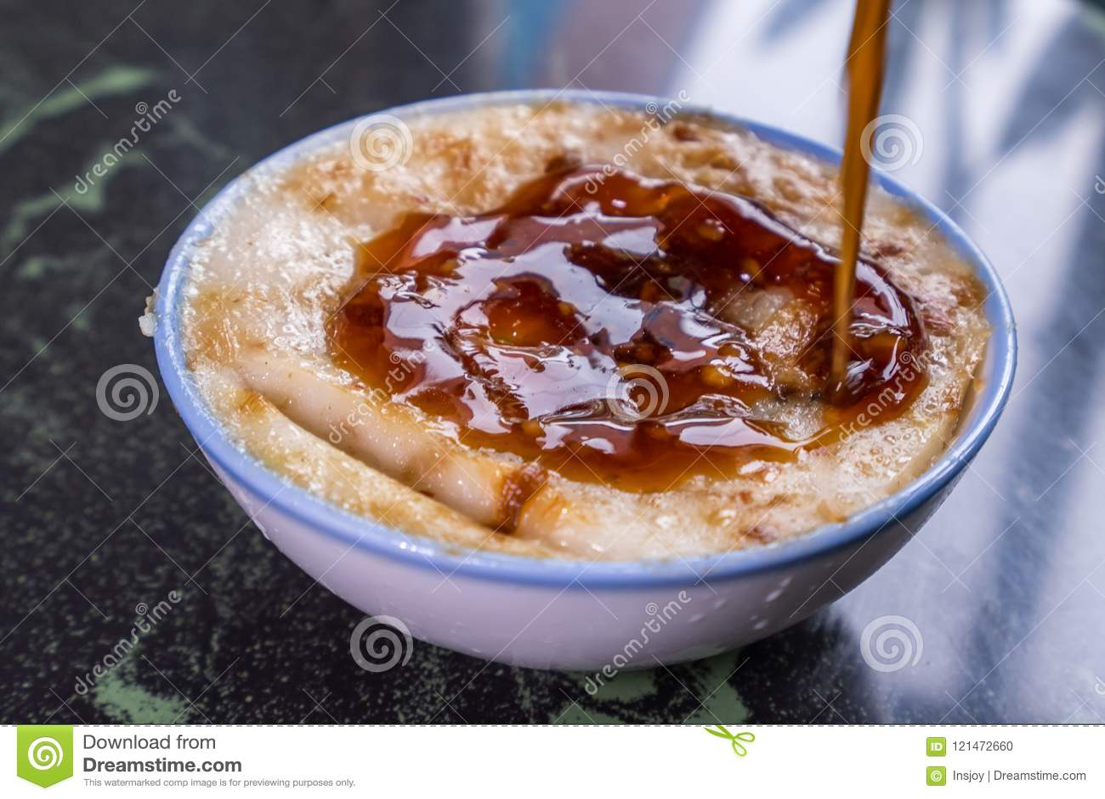 Διακριτικά διάσημα πρόχειρα φαγητά της Ταϊβάν ` s: Αλμυρό gui Wa πουτίγκας ρυζιού σε ένα άσπρο κύπελλο στον πίνακα πετρών, λιχουδ