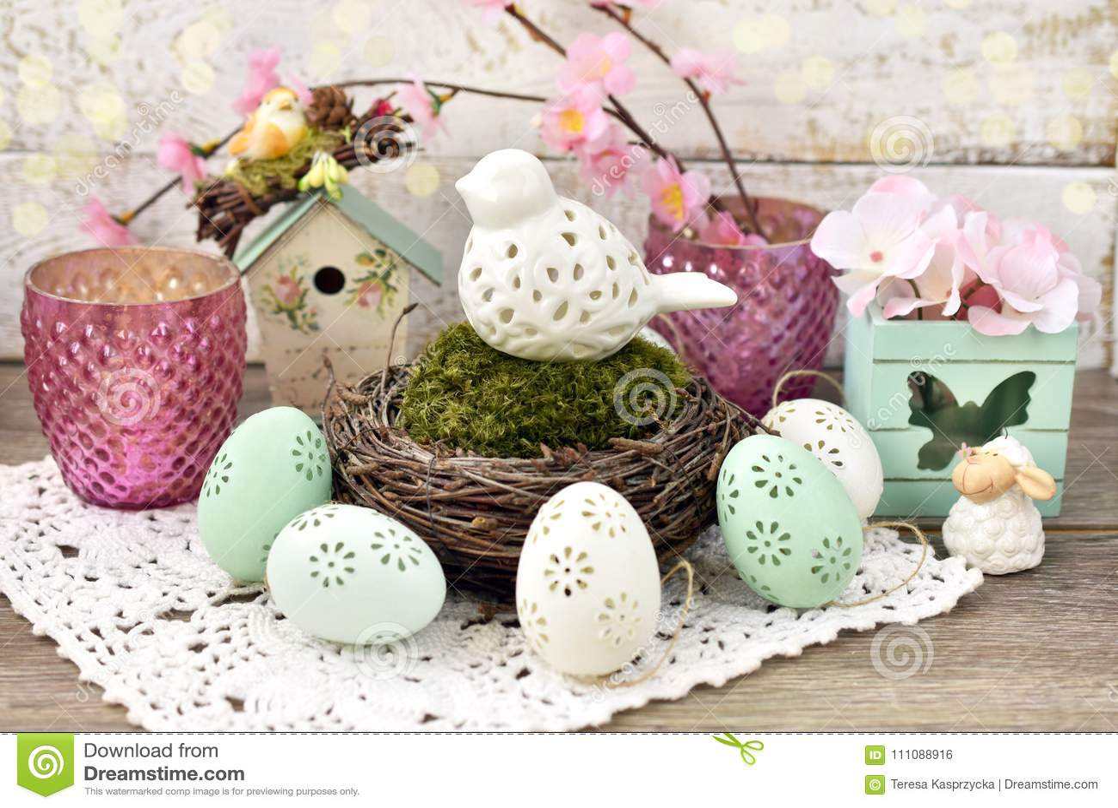 Διακόσμηση Πάσχας με το πουλί πορσελάνης στη φωλιά και τα αυγά