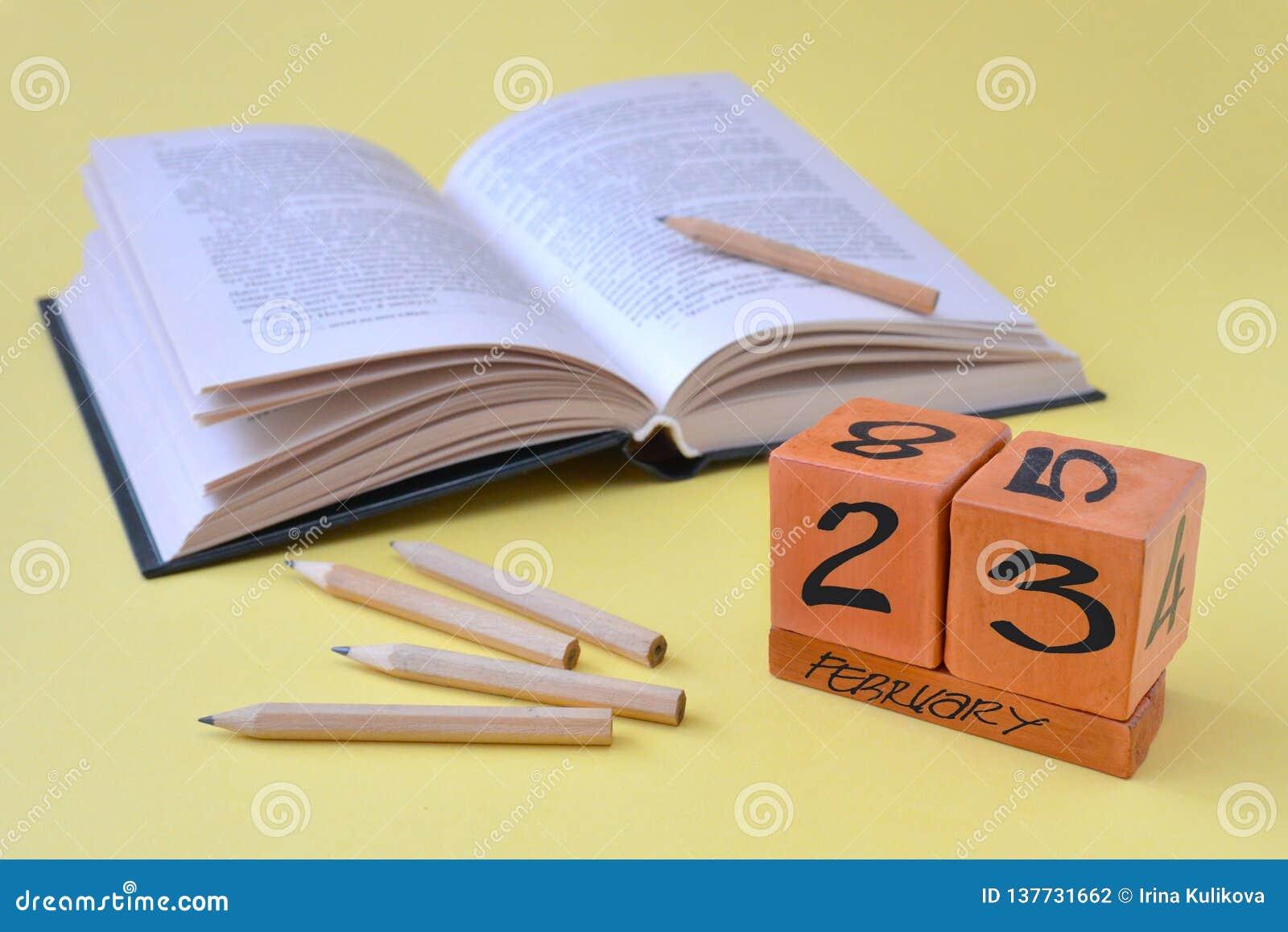 Διαρκές ξύλινο ημερολόγιο με την ημερομηνία της 23ης Φεβρουαρίου, ενός ανοιγμένου βιβλίου και των μολυβιών σε ένα κίτρινο υπόβαθρ