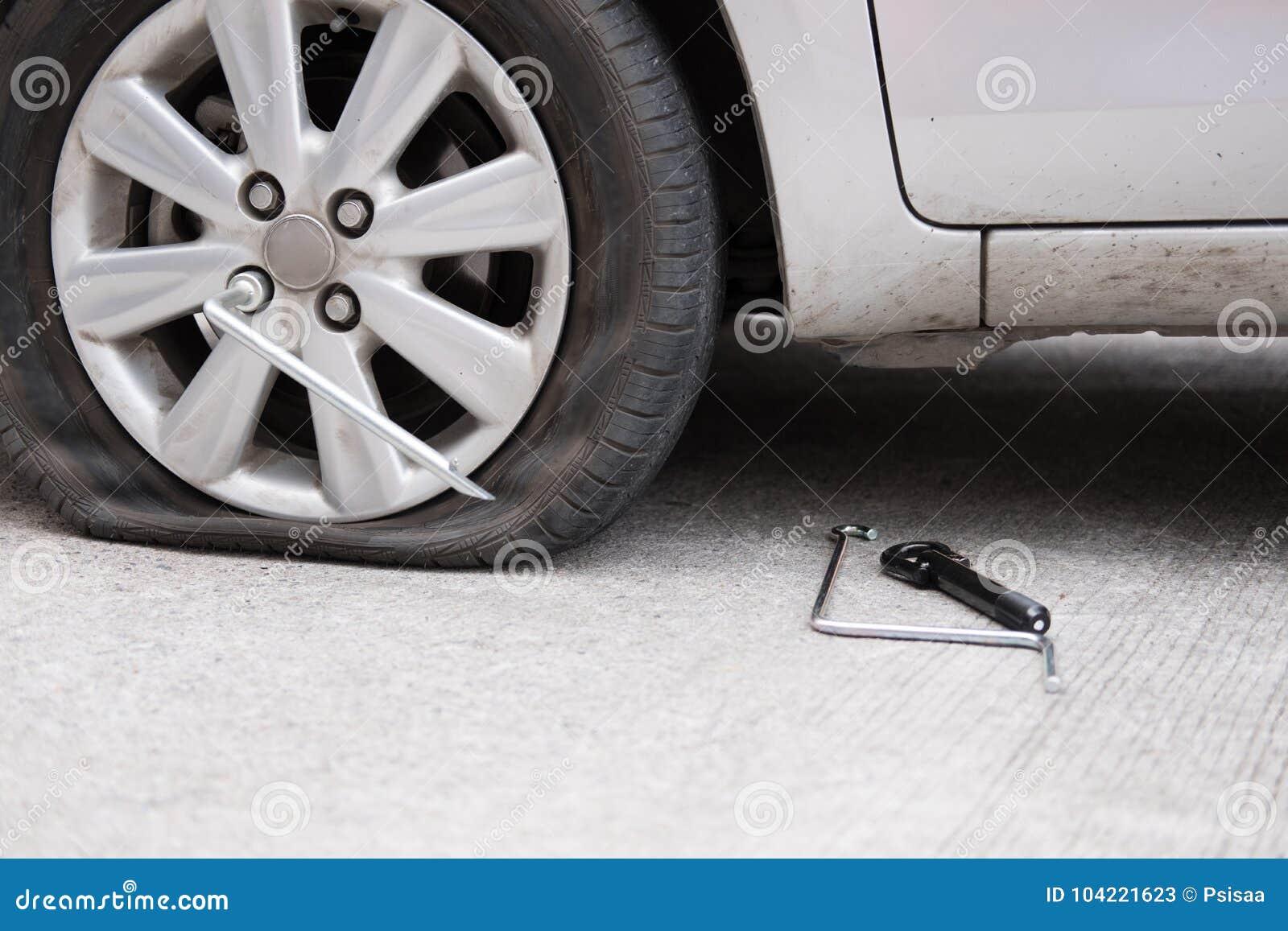 Διαρροή ροδών αυτοκινήτων λόγω του σφυροκοπήματος καρφιών επίπεδο ελαστικό αυτοκινήτου στο δρόμο flatt